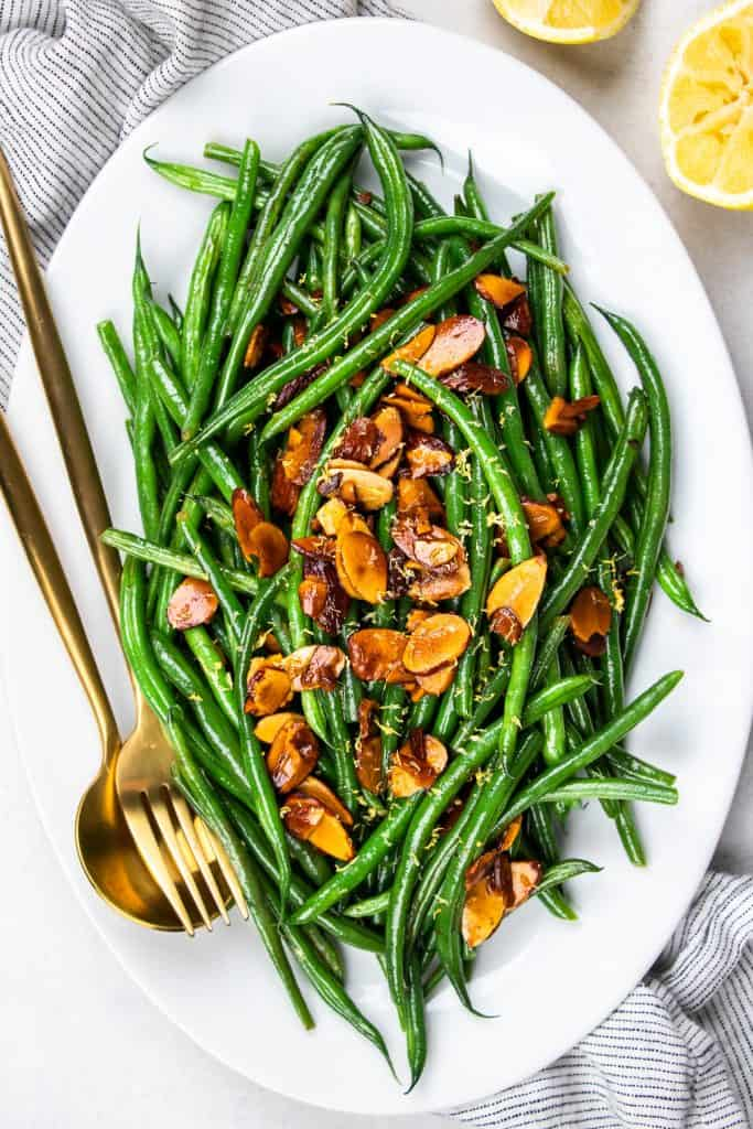 Green beans amandine topped with toasted alonds on a white oval plate.