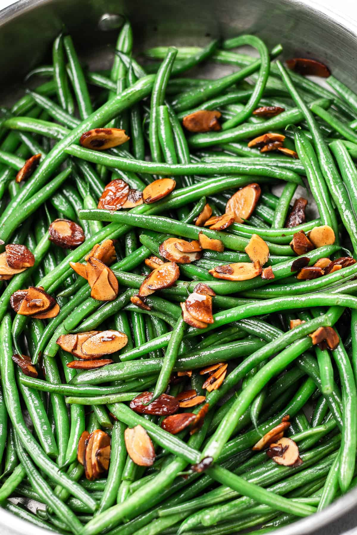 Green beans amandine topped with toasted alonds in a skillet.