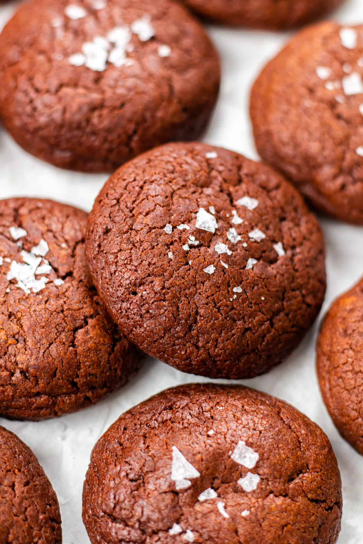 Brownie cookies, topped with flaky salt on white table.