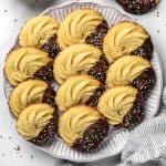 Danish Butter cookies, half covered with chocolate and sprinkles on a white plate.