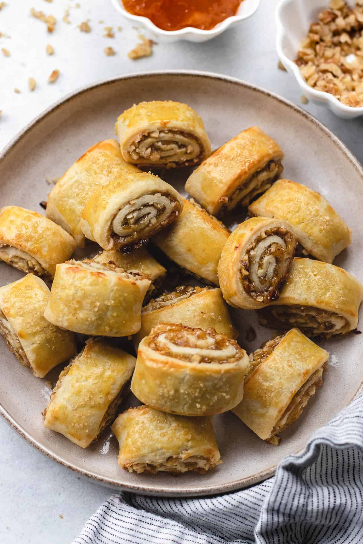 Baked Apricot rugelach cookies on a round plate, with a towel, chopped walnuts and jam on the side.