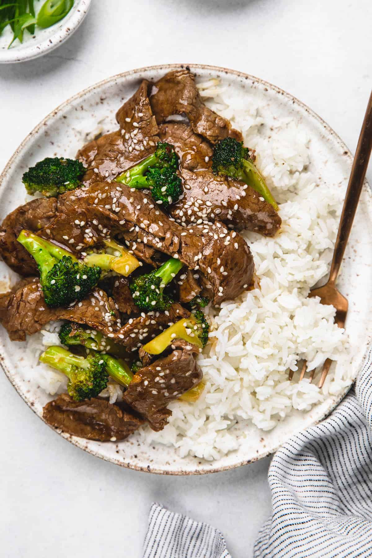 Beef and broccoli with rice on a white plate with golden fork.