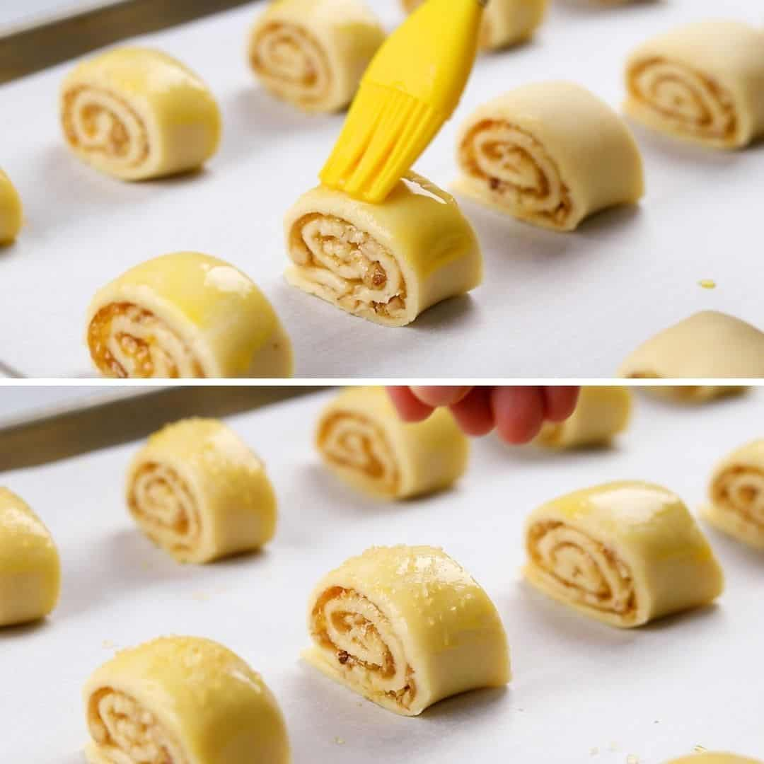 Brushing Rugelach cookies with egg wash on a baking sheet with parchment papper.