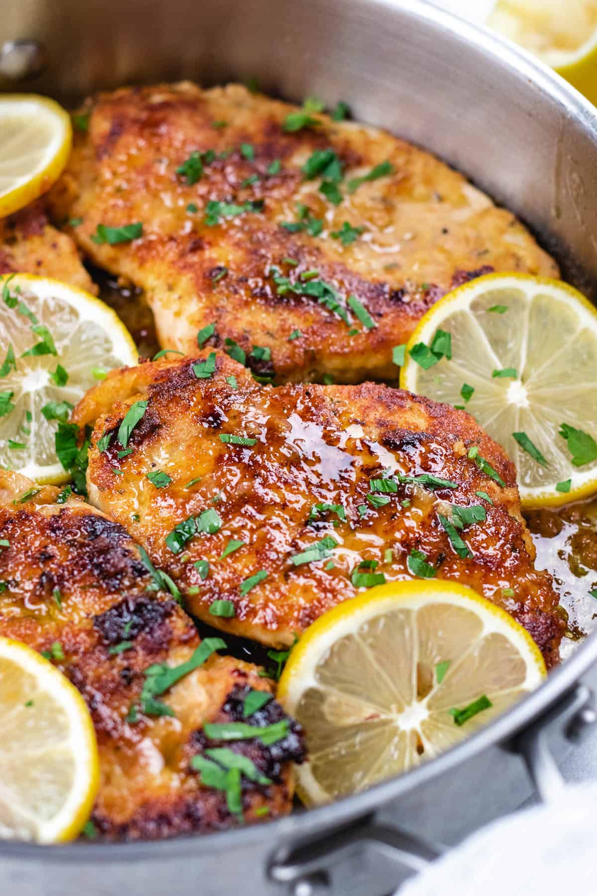 Chicken breasts with lemon sauce in a skillet with lemon slices.