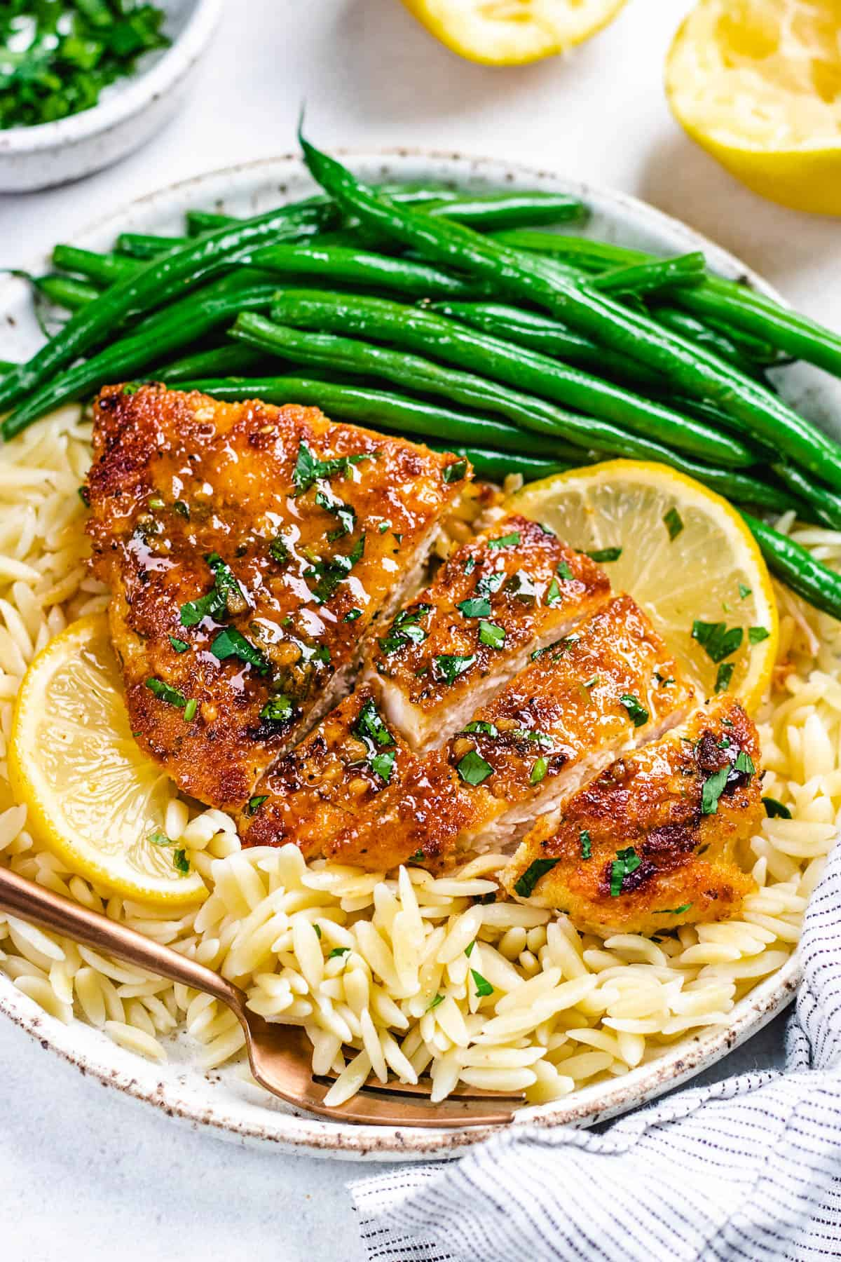 Chicken breast with orzo and green beans on a white plate.