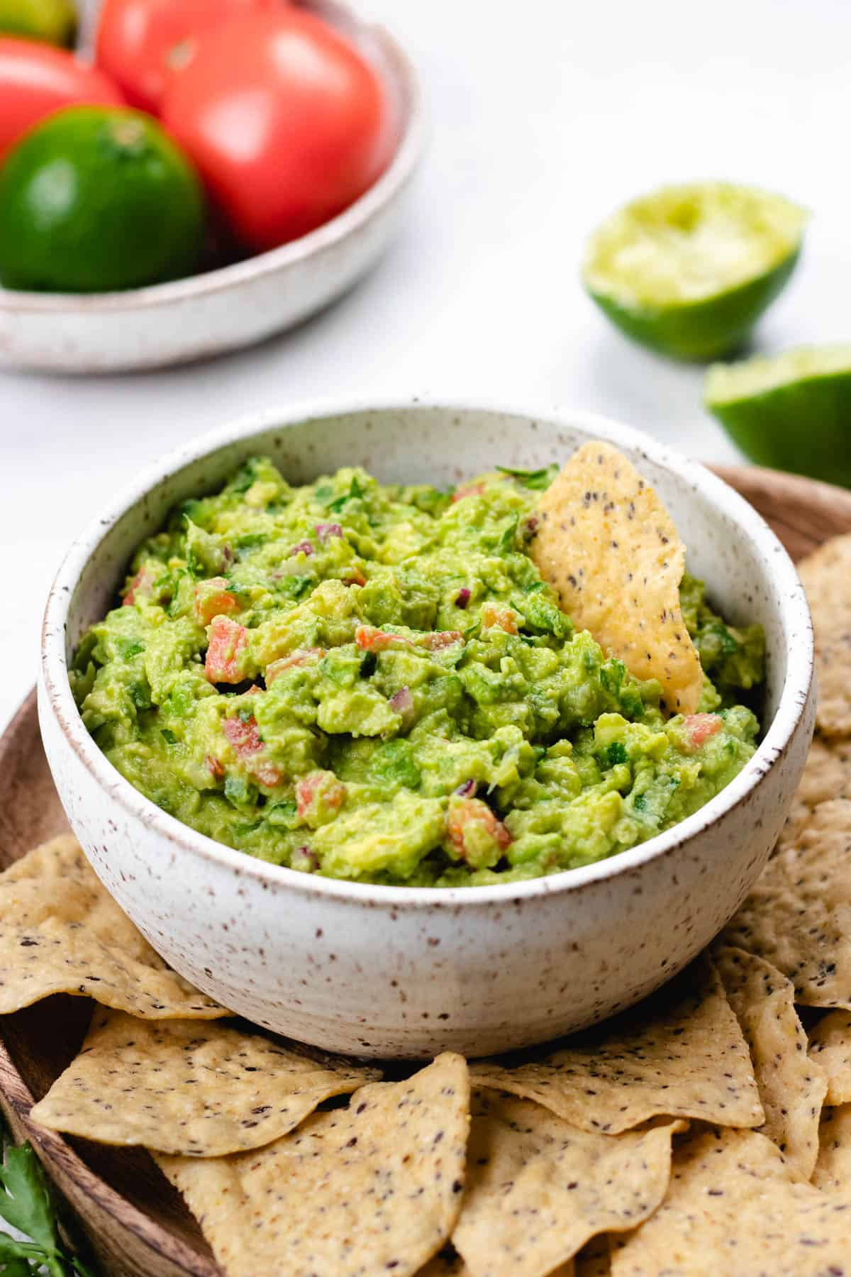 Guacamole in a white bowl with tortillas around it.