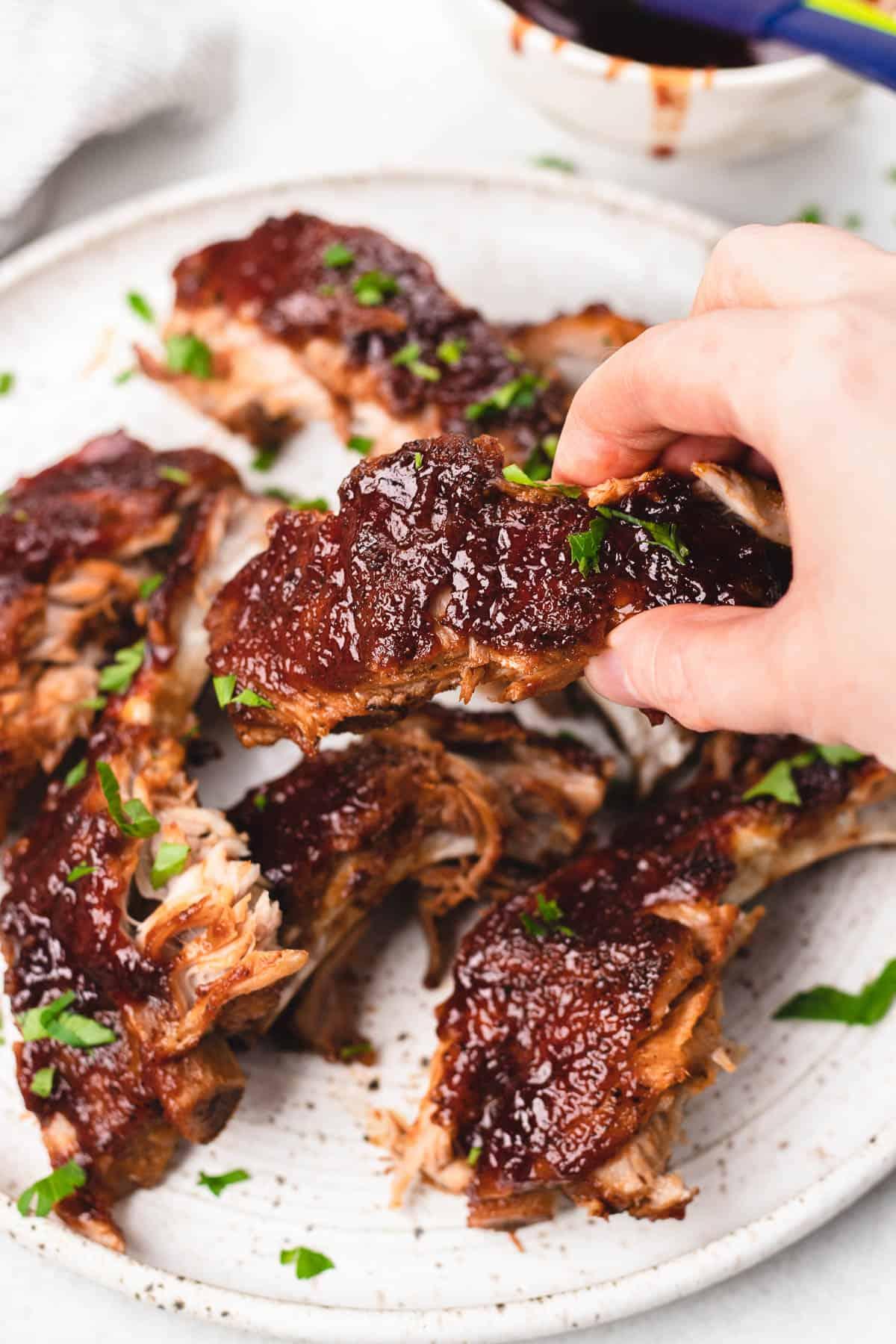 Precut BBQ Ribs on a white plate.