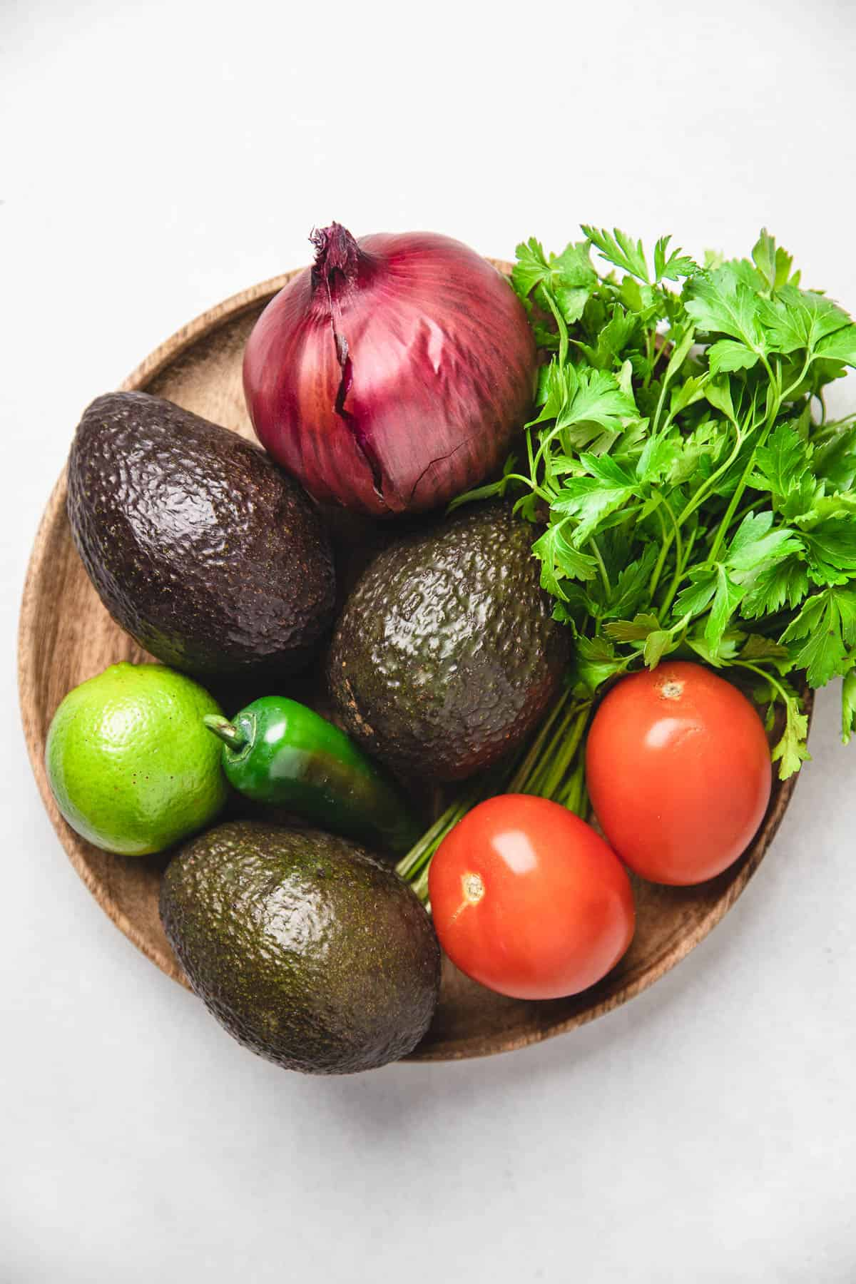 Vegetables on a wooden plate. Ingredients for guacamole.
