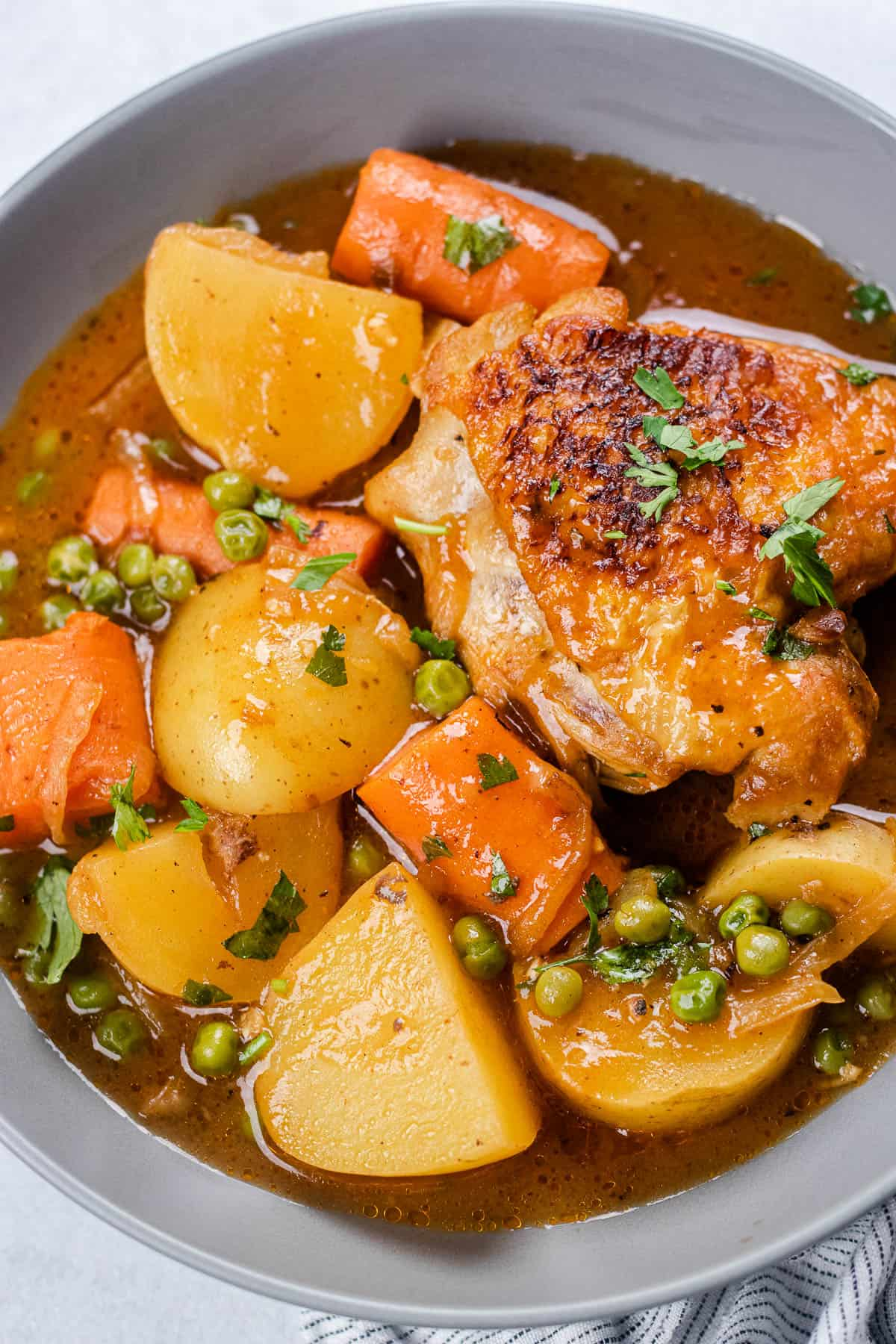 Chicken thigh with potatoes and vegetables in a grey bowl.