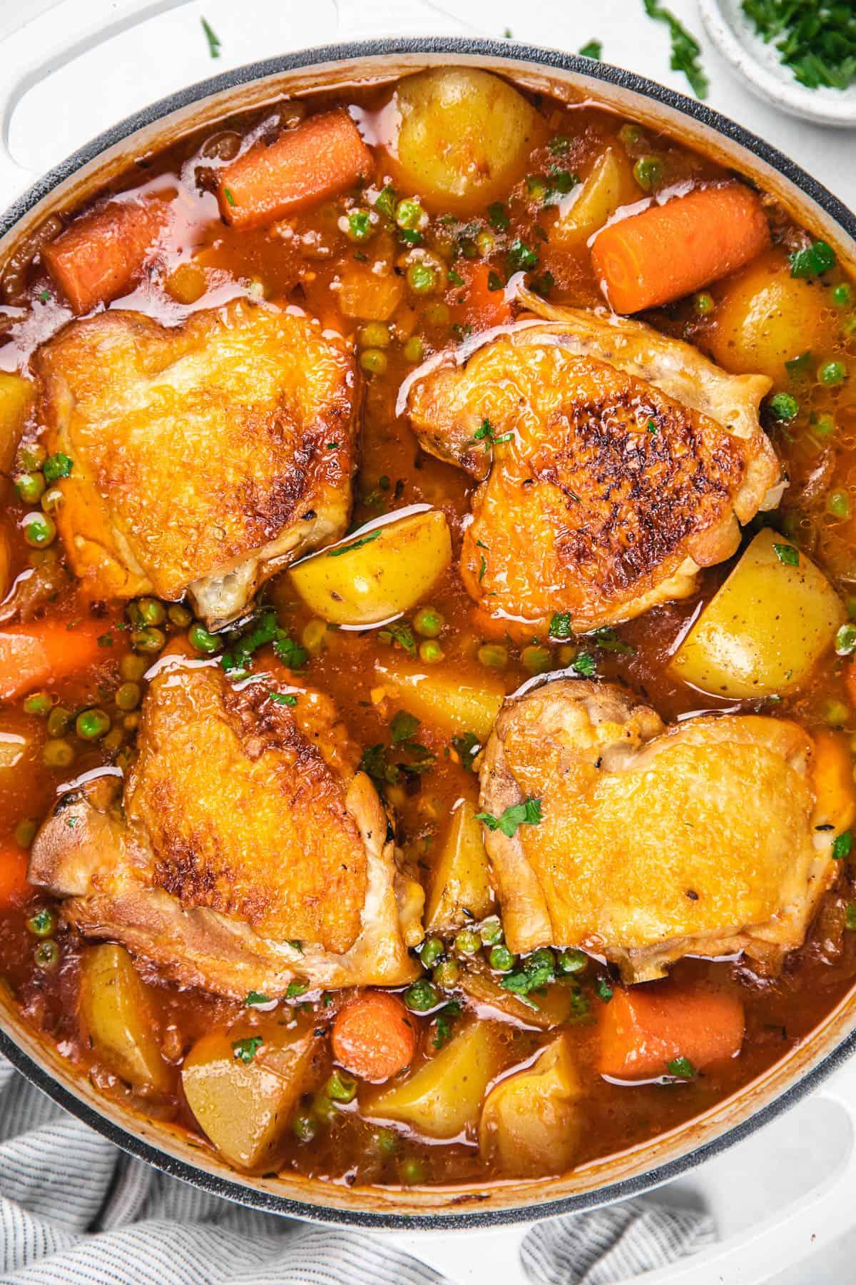 Chicken stew in a white casserole dish.