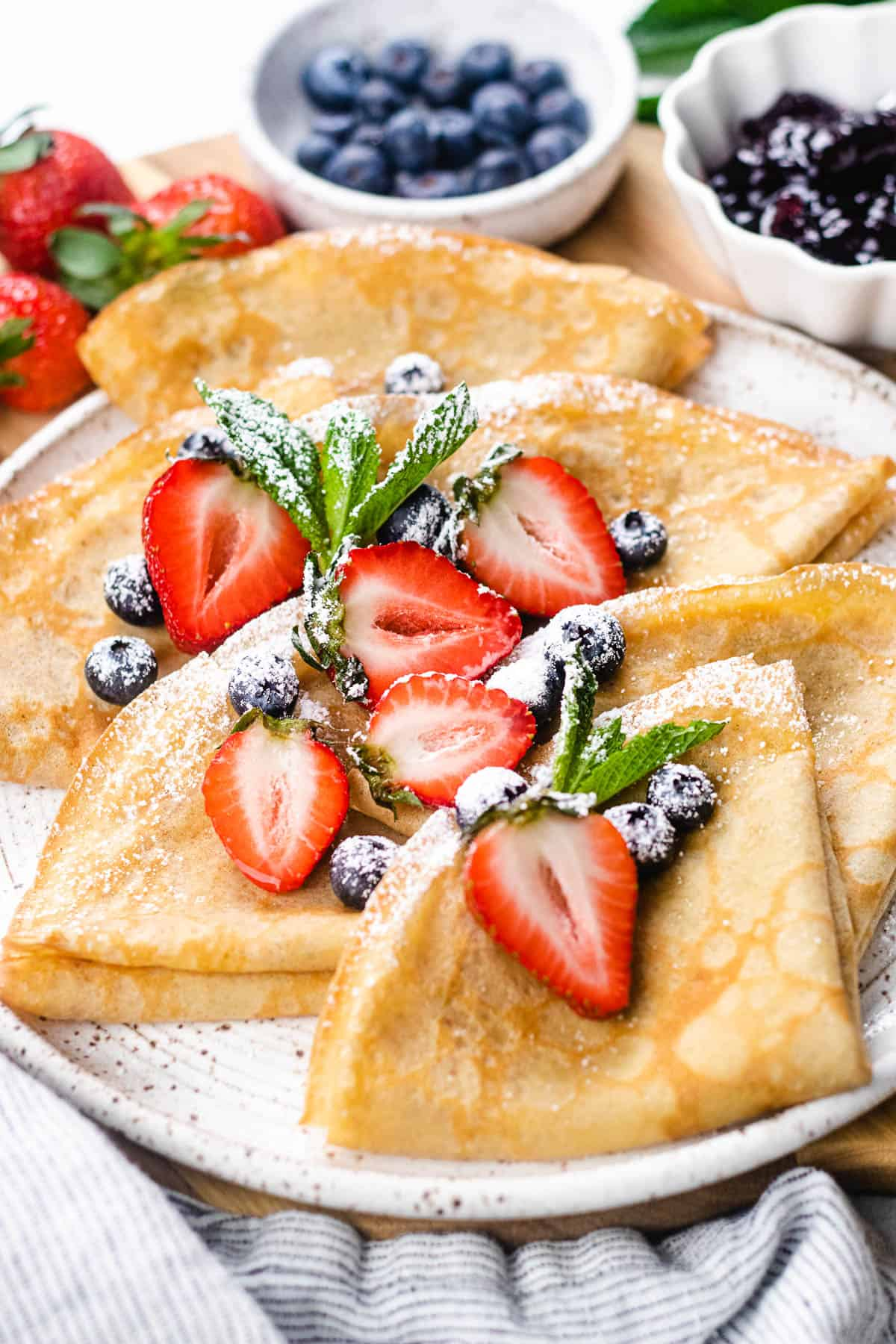 Folded crepes, topped with berries and powdered sugar.