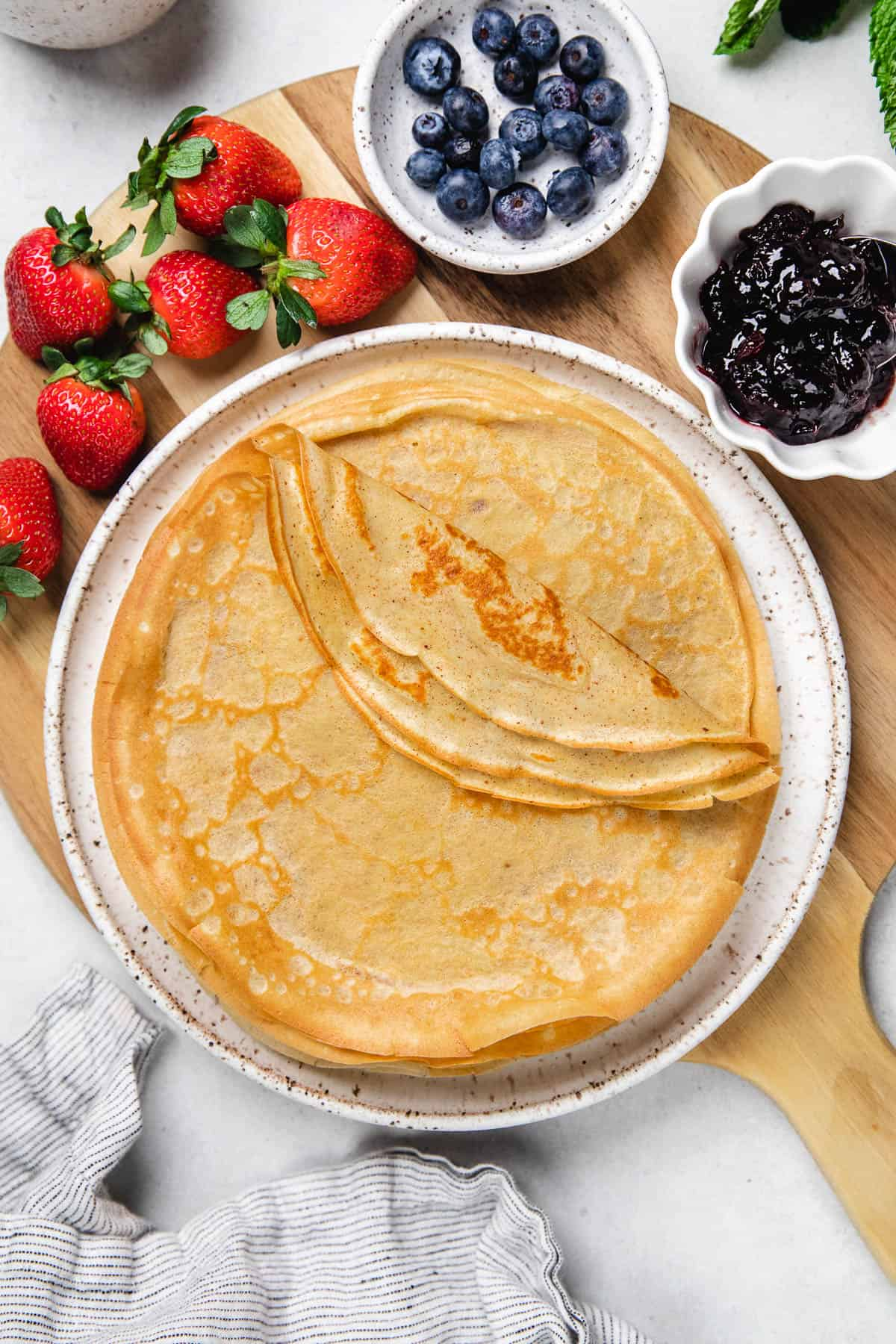 Crepes on a plate with berries and jam.
