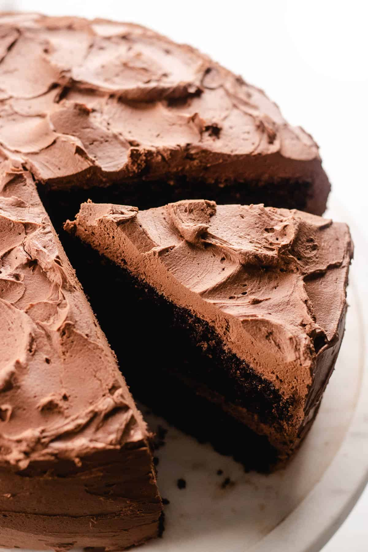 A precut chocolate cake on a platter.