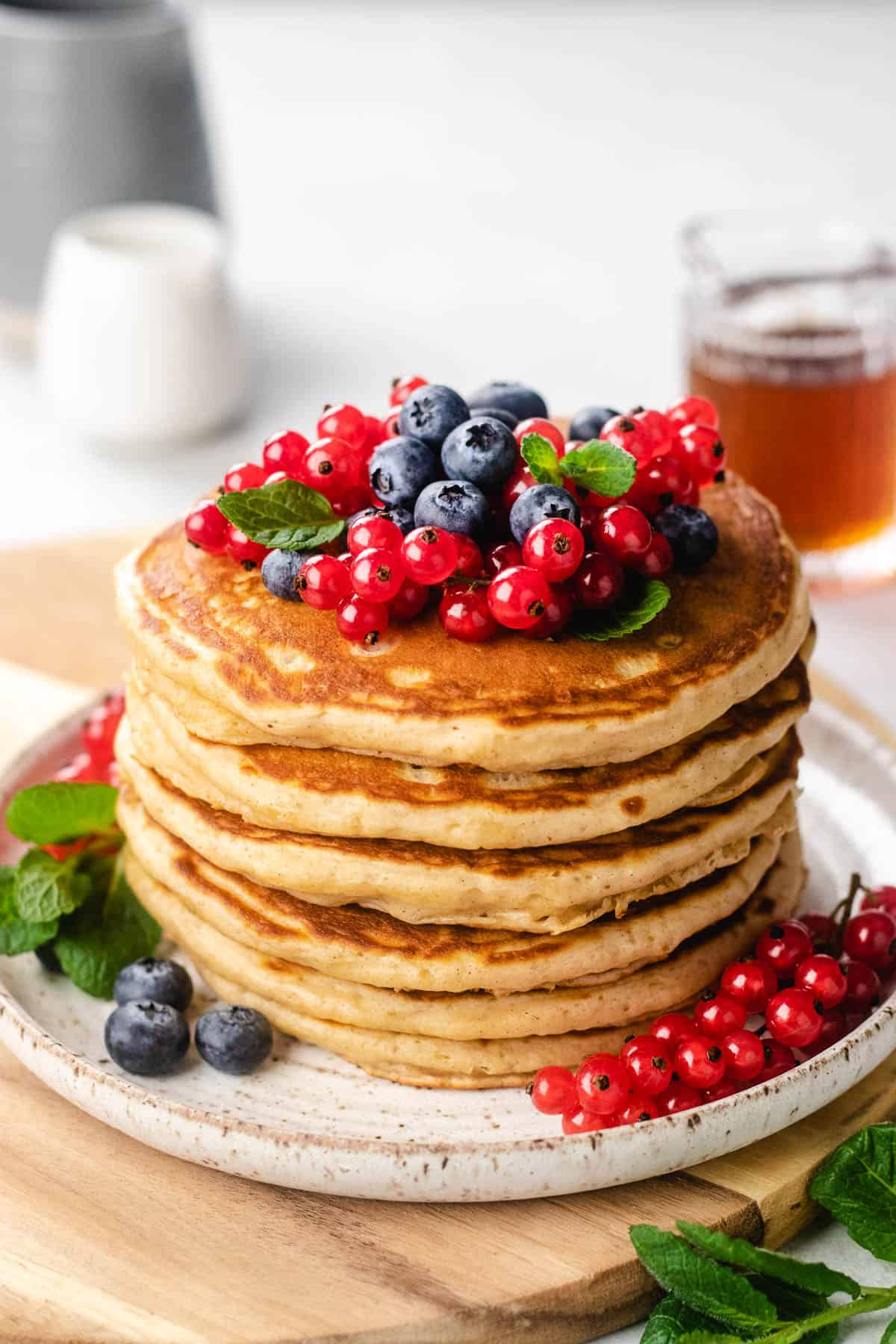 A stack of pancakes, topped with berries on a plate.