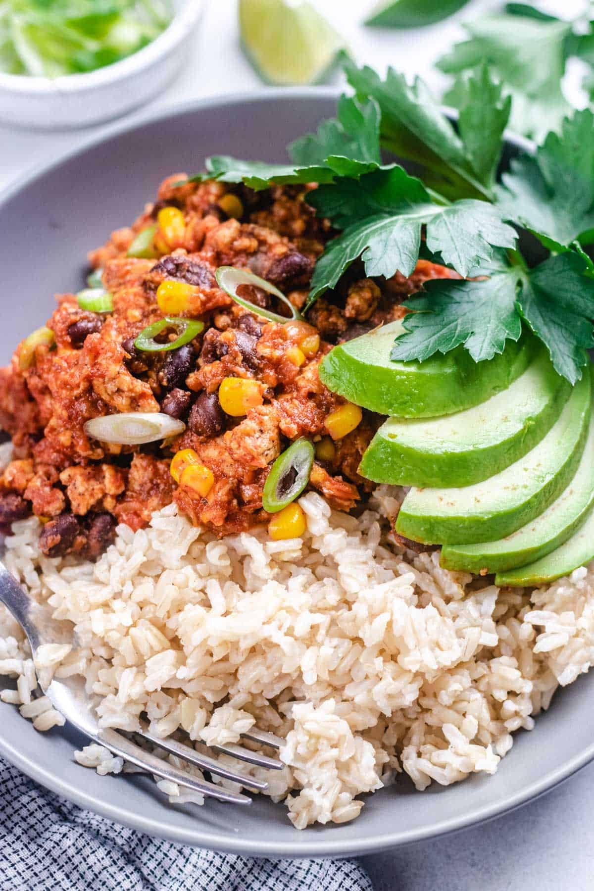 Turkey taco skillet with brown rice, topped with avocado and cilantro.