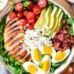 Diced chicken, eggs, avocado, chrry tomatoes, lettuce, and feta cheese in a bowl.