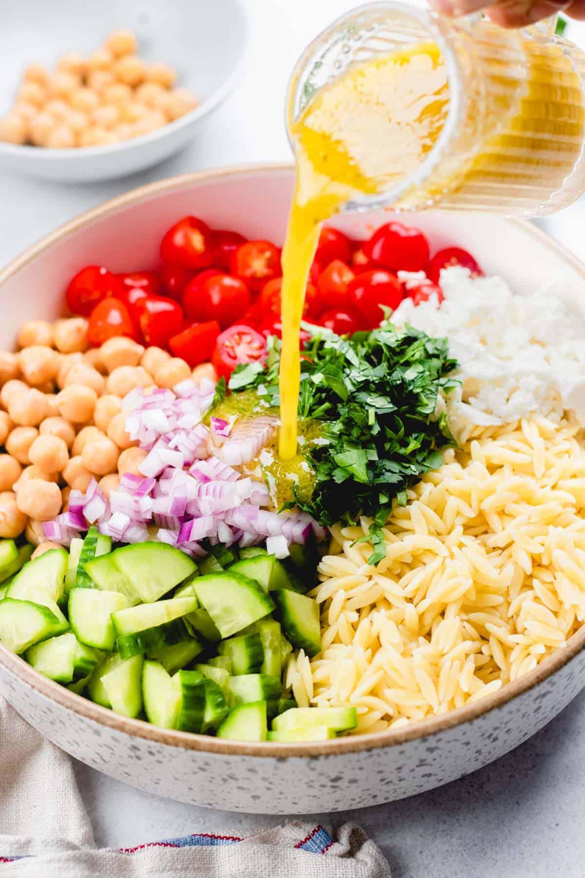 Pouring vinaigrette into the salad.