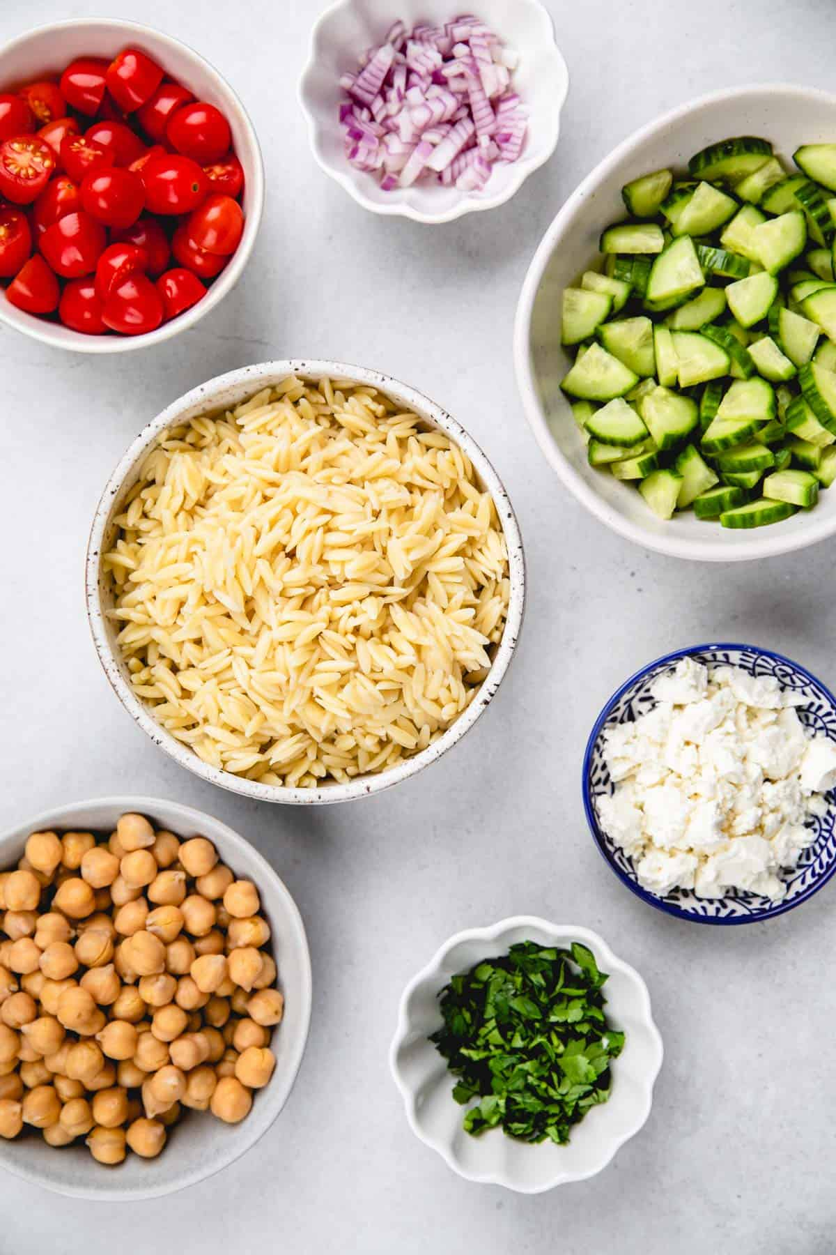 Prepped ingredients for orzo salad in separate bowls.
