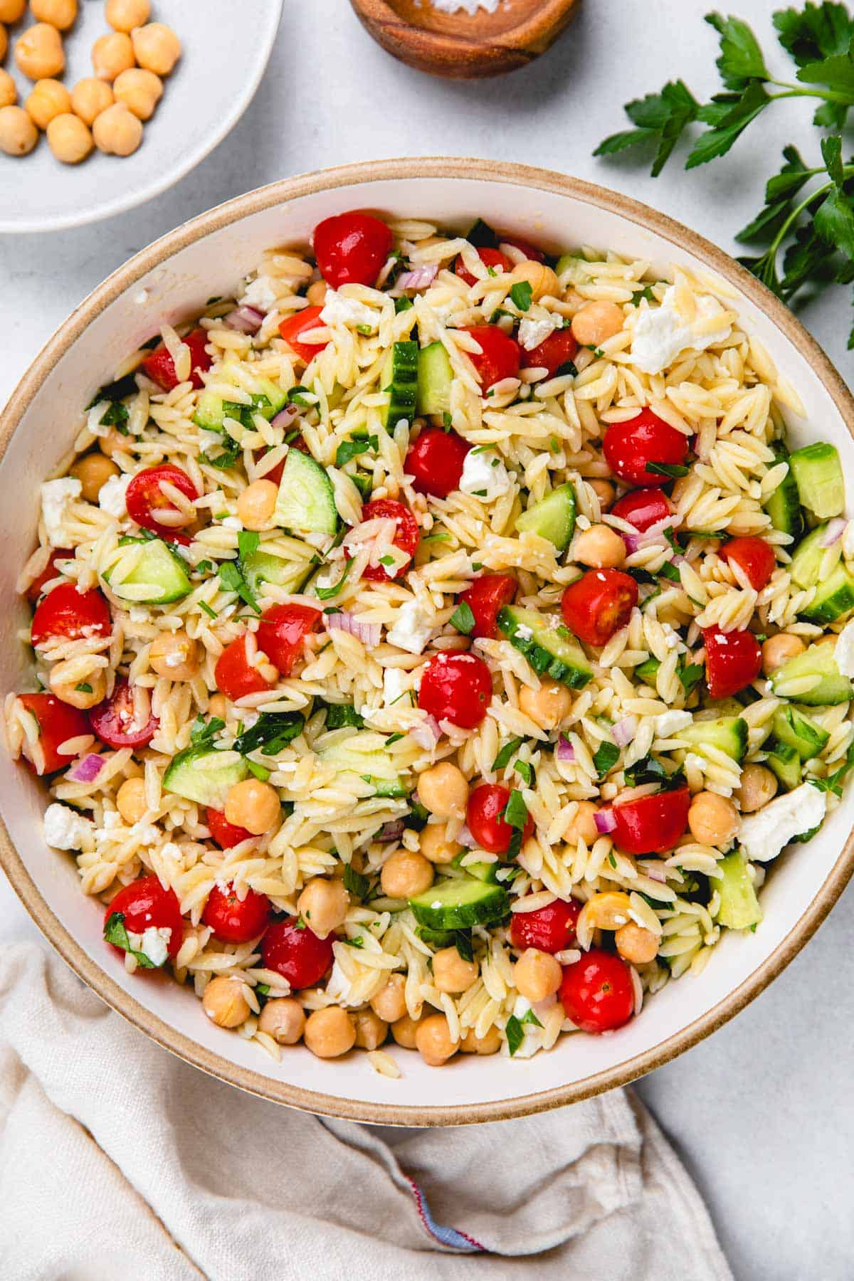 Salad with orzo, cucumbers, cherry tomatoes in a large bowl.