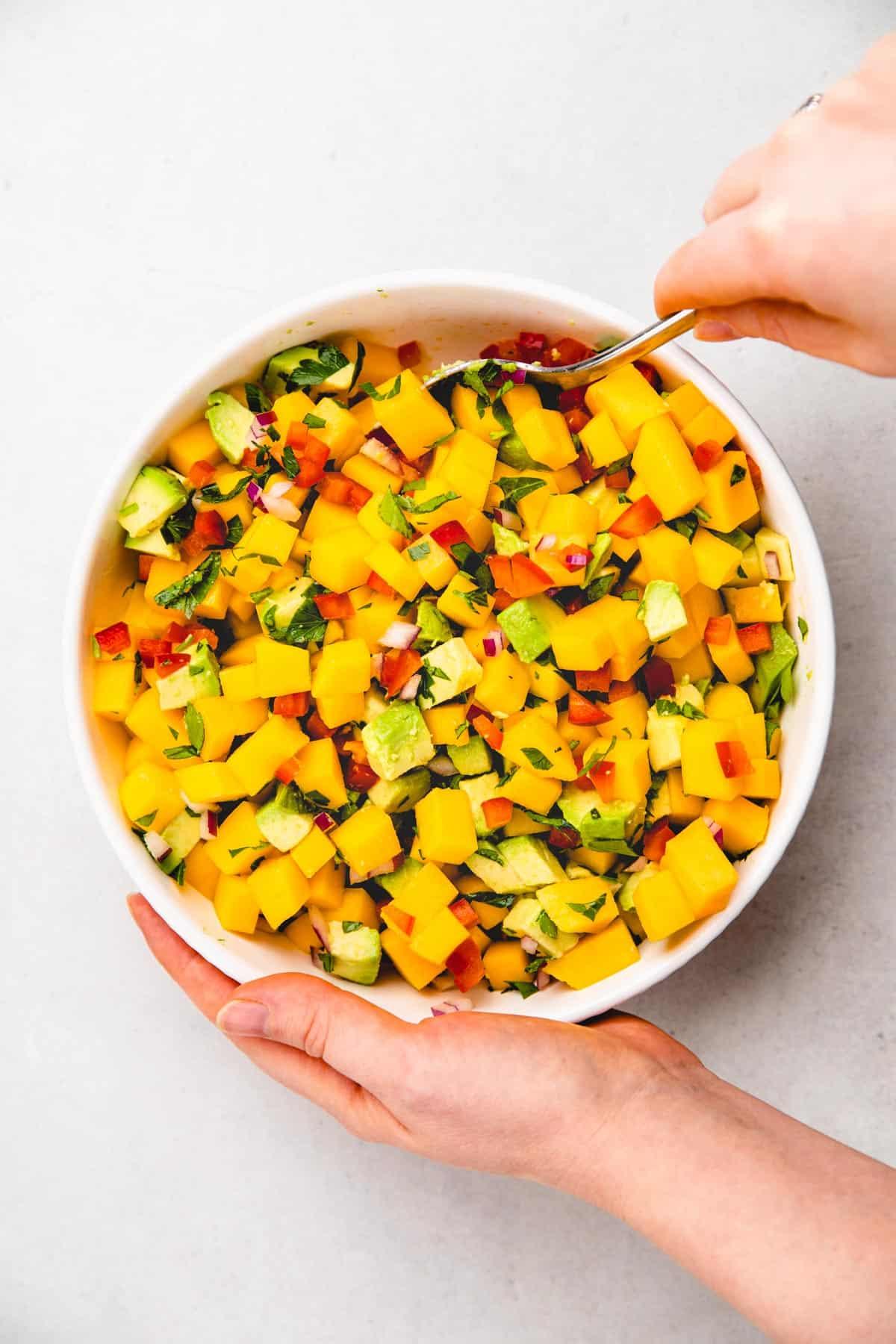 Mixing mango avocado salsa.