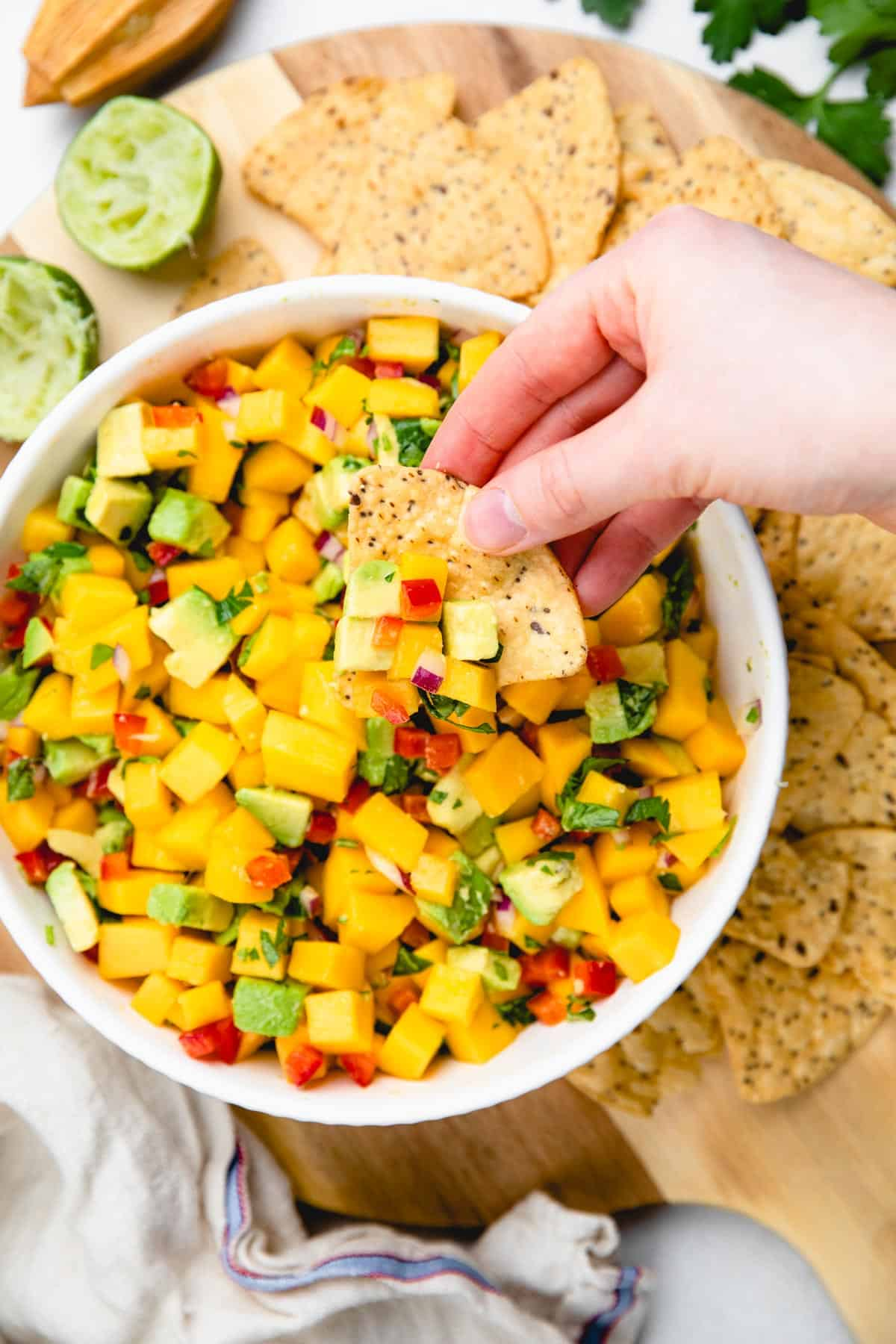 Mango Avocado Salsa with tortilla chips on a cutting board.