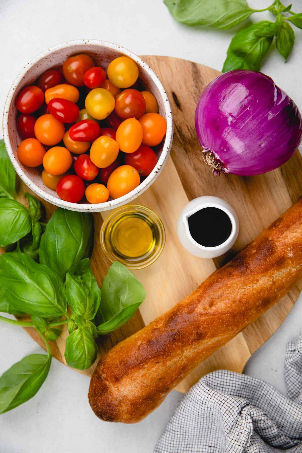 Ingredients for bruschetta (cherry tomatoes, red onion, basil, baguette, olive oil, balsamic glaze.