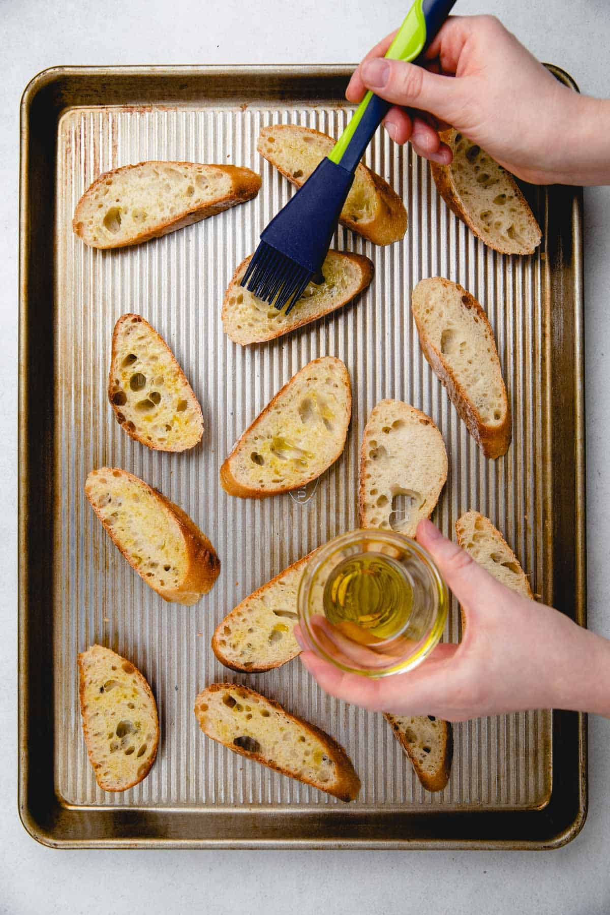 Brushing baguette slices with olive oil.