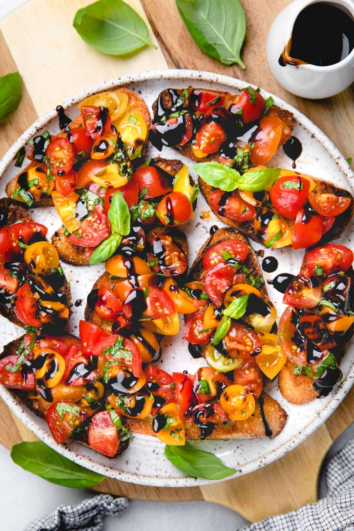 Cherry tomato bruschetta drizzled with balsamic glaze on a white plate.