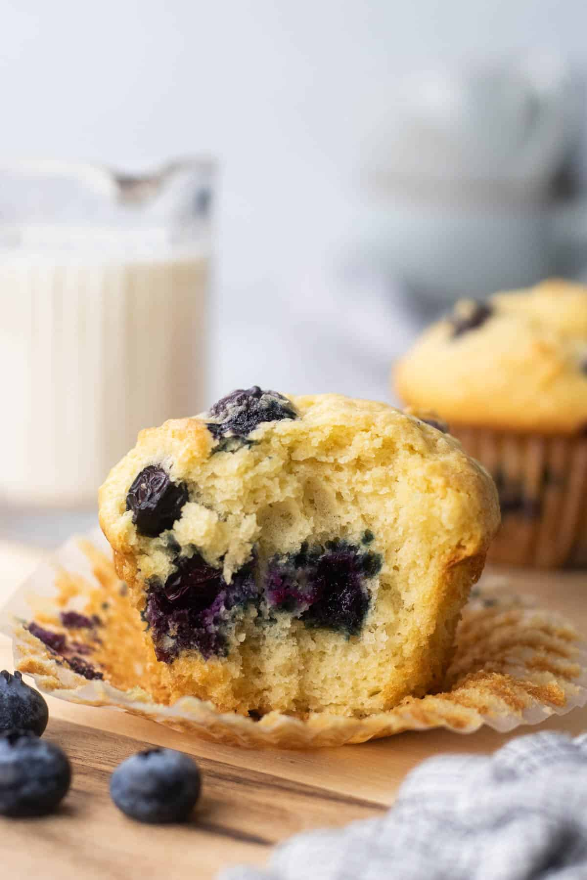 A bite shot of a blueberry muffins on a cutting board.