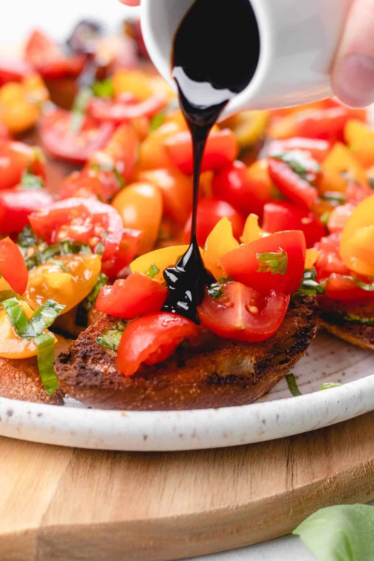 Pouring balsamic glaze on top of bruschetta.