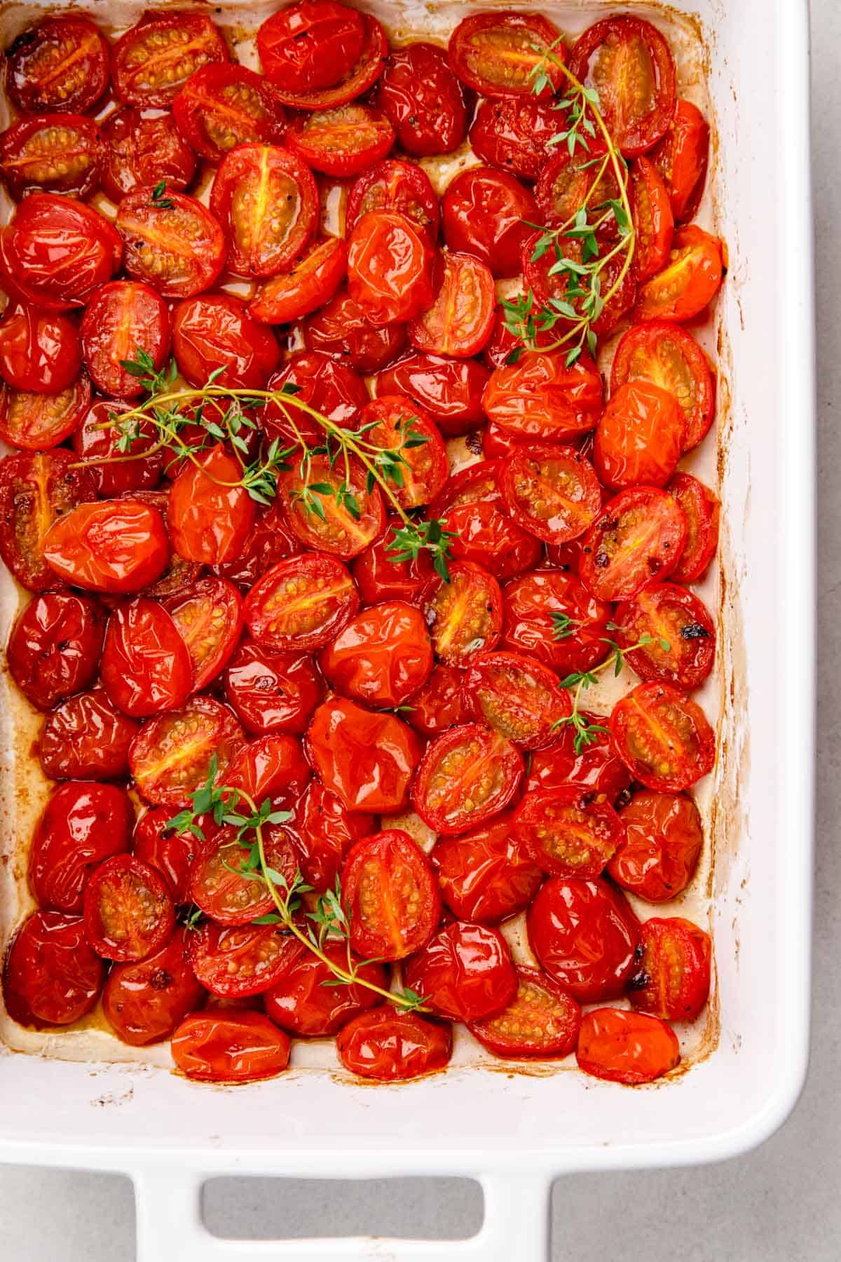 Roasted halved red cherry tomatoes in a white baking pan, topped with fresh thyme.