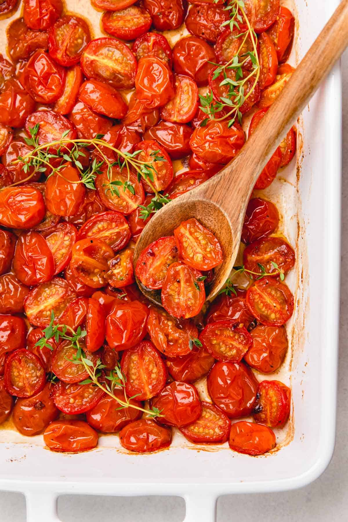 Roasted halved red cherry tomatoes in a white baking pan with a wooden spoon.