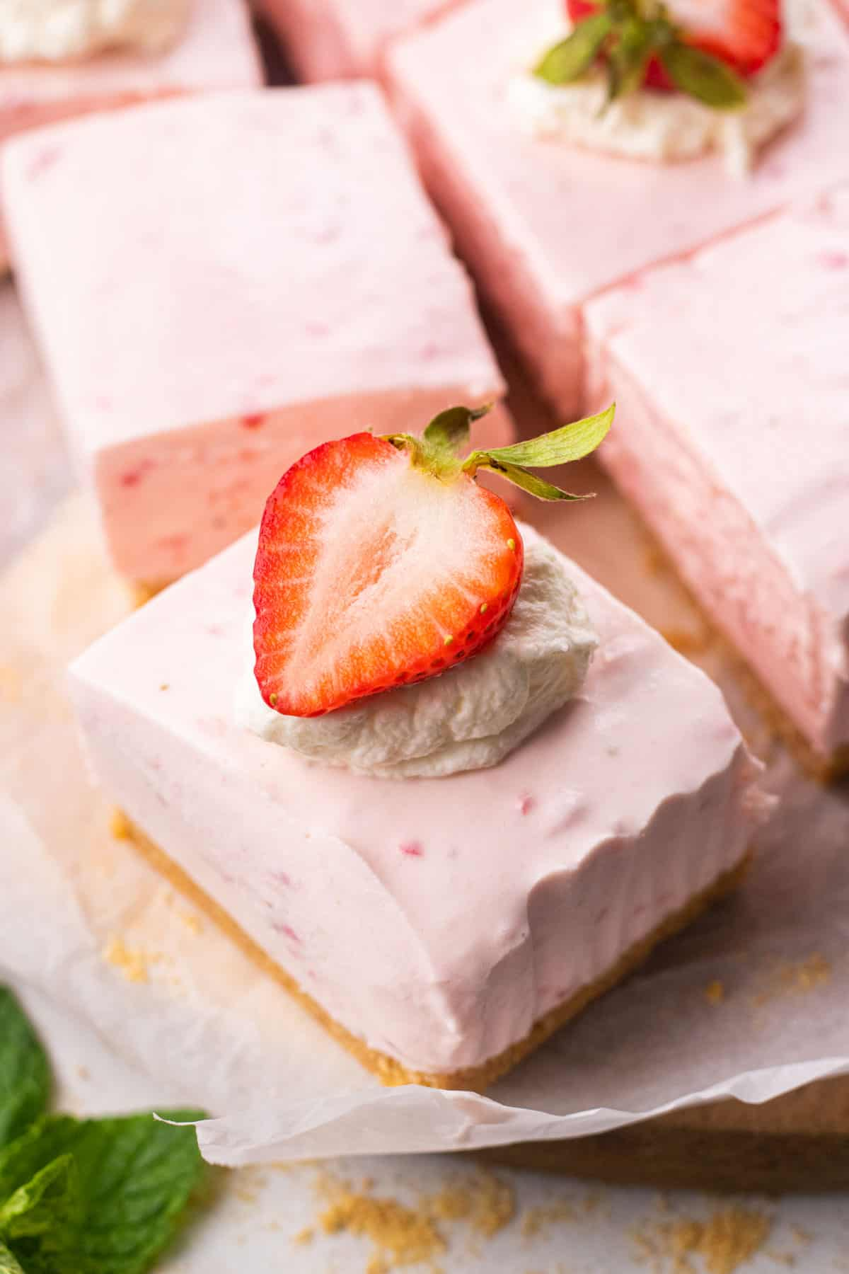 Strawberry cheesecake bar, topped with whipped cream and a strawberry.