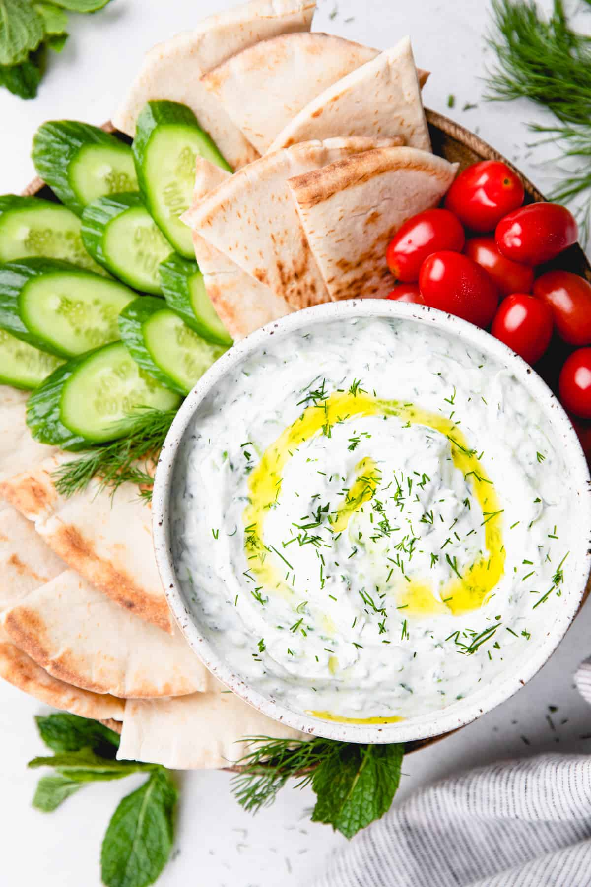 Tzatziki sauce, topped with olive oil and chopped dill, in a white bowl and vegetables and pita bread around it.