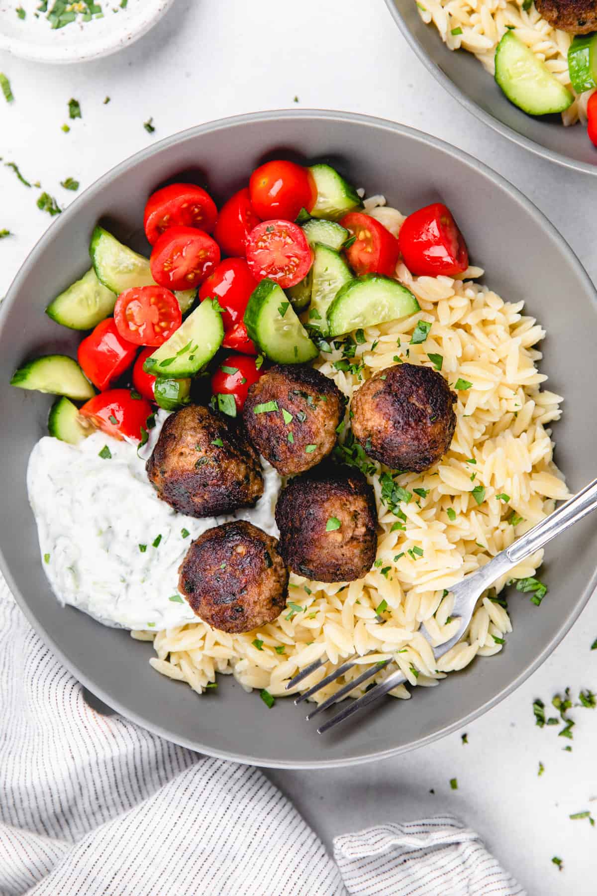 Greek meatballs with orzo, tzatziki sauce, and cherry cucumber salad in a grey bowl with a fork.