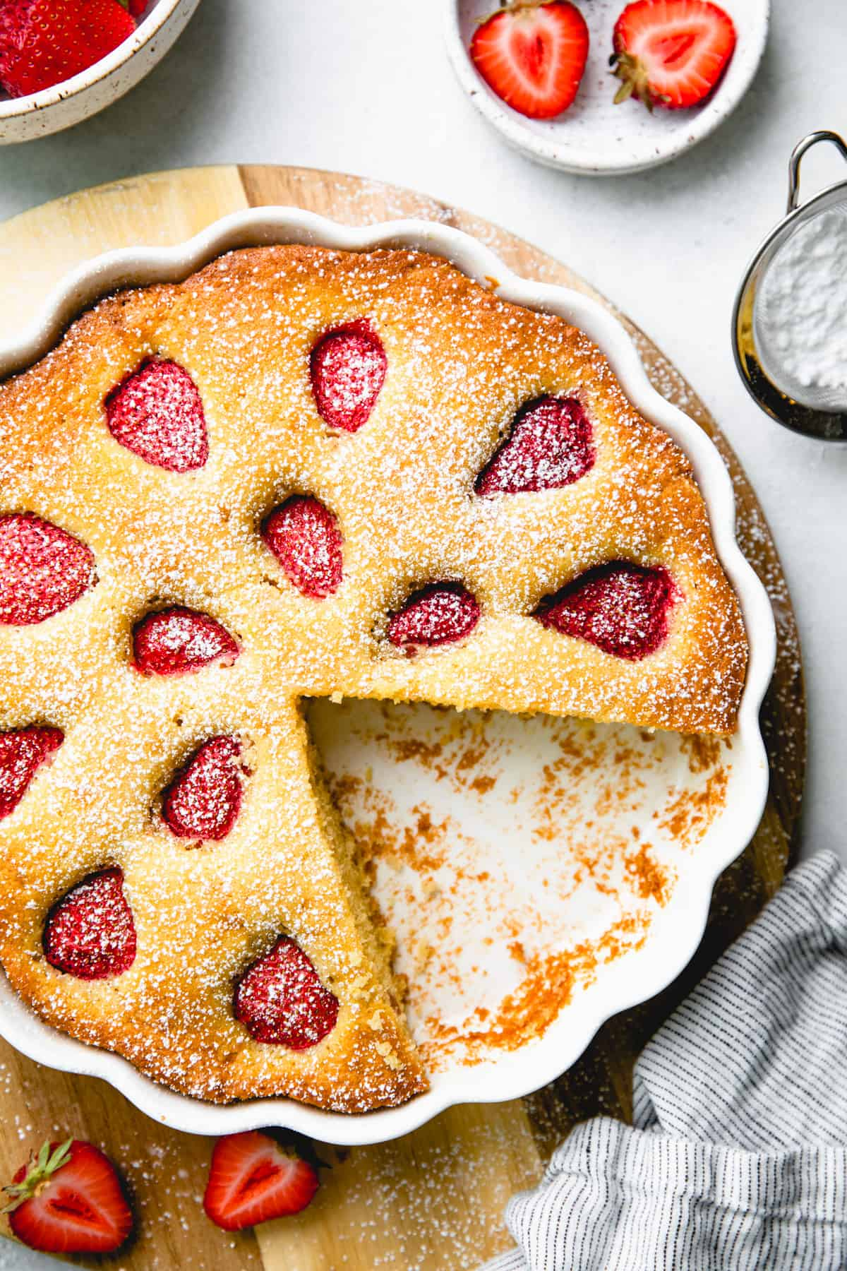 A vanilla coffee cake, topped with strawberries, in a white round baking pan on a wooden board.