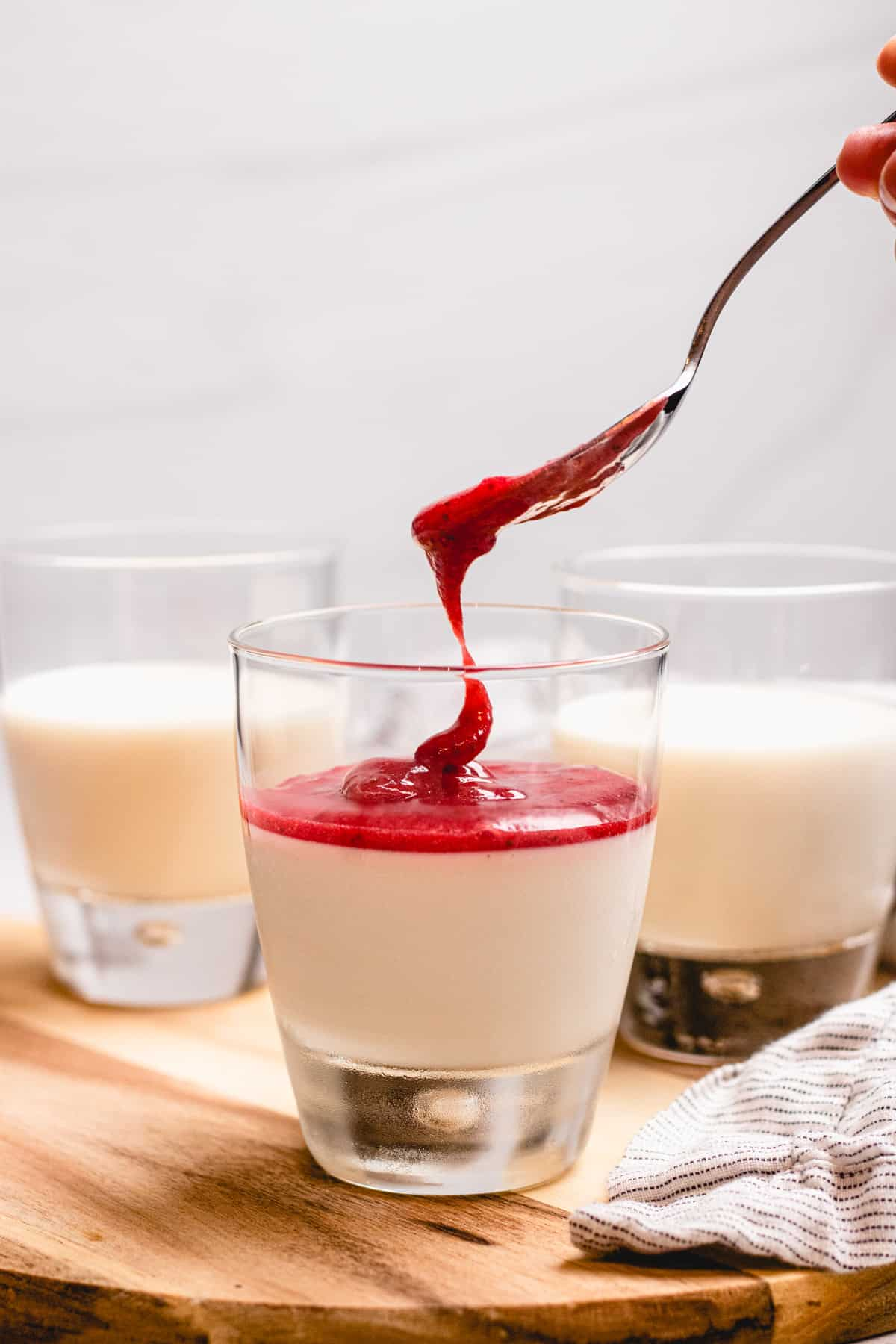 Pouring strawberry sauce in a glass with panna cotta.