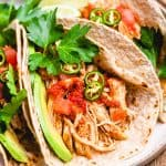 Tacos with shredded chicken, tomatoes, avocado, jalapeno, and cilantro on a plate.