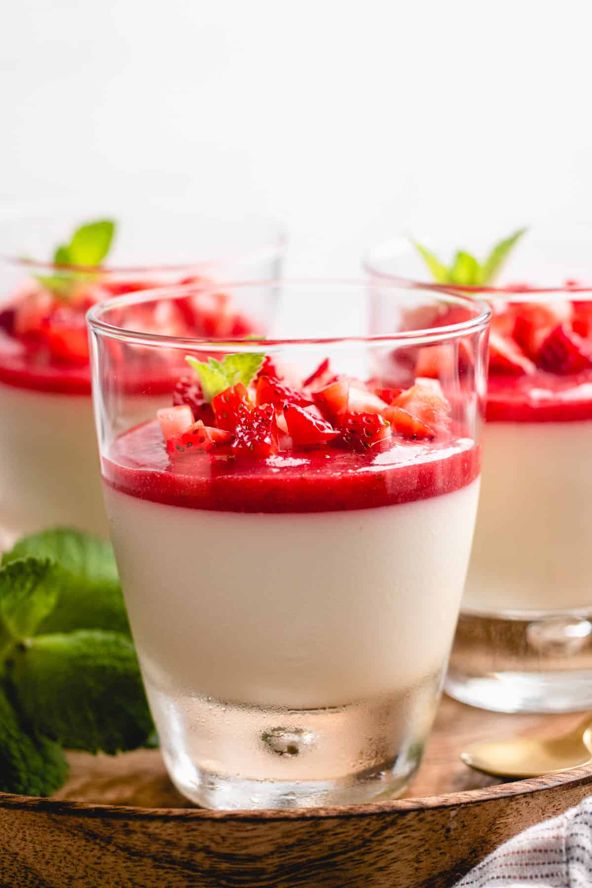 3 glasses with Panna Cotta topped with strawberry sauce on a wooden tray.
