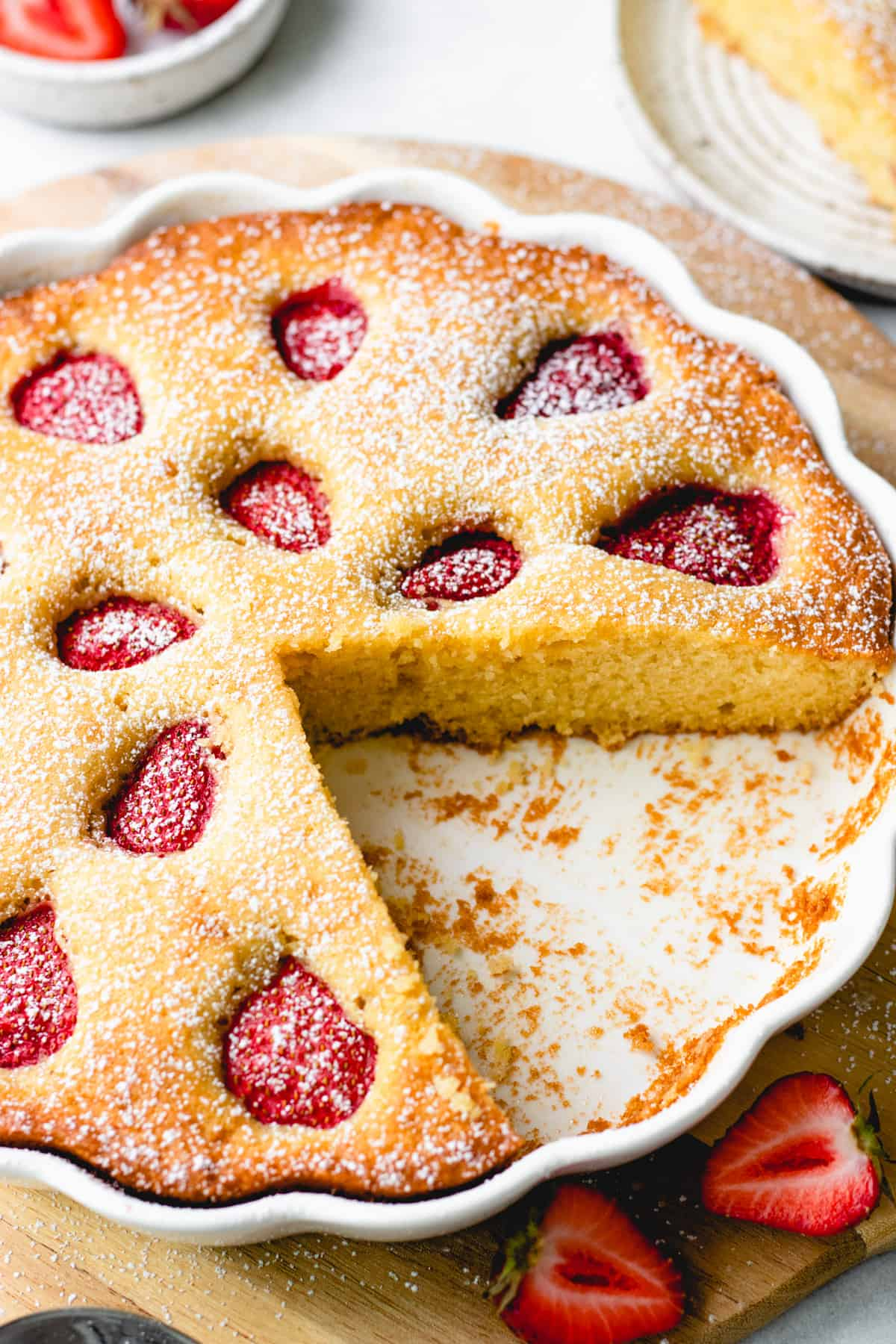 A sliced vanilla coffee cake, topped with strawberries, in a white round baking pan.