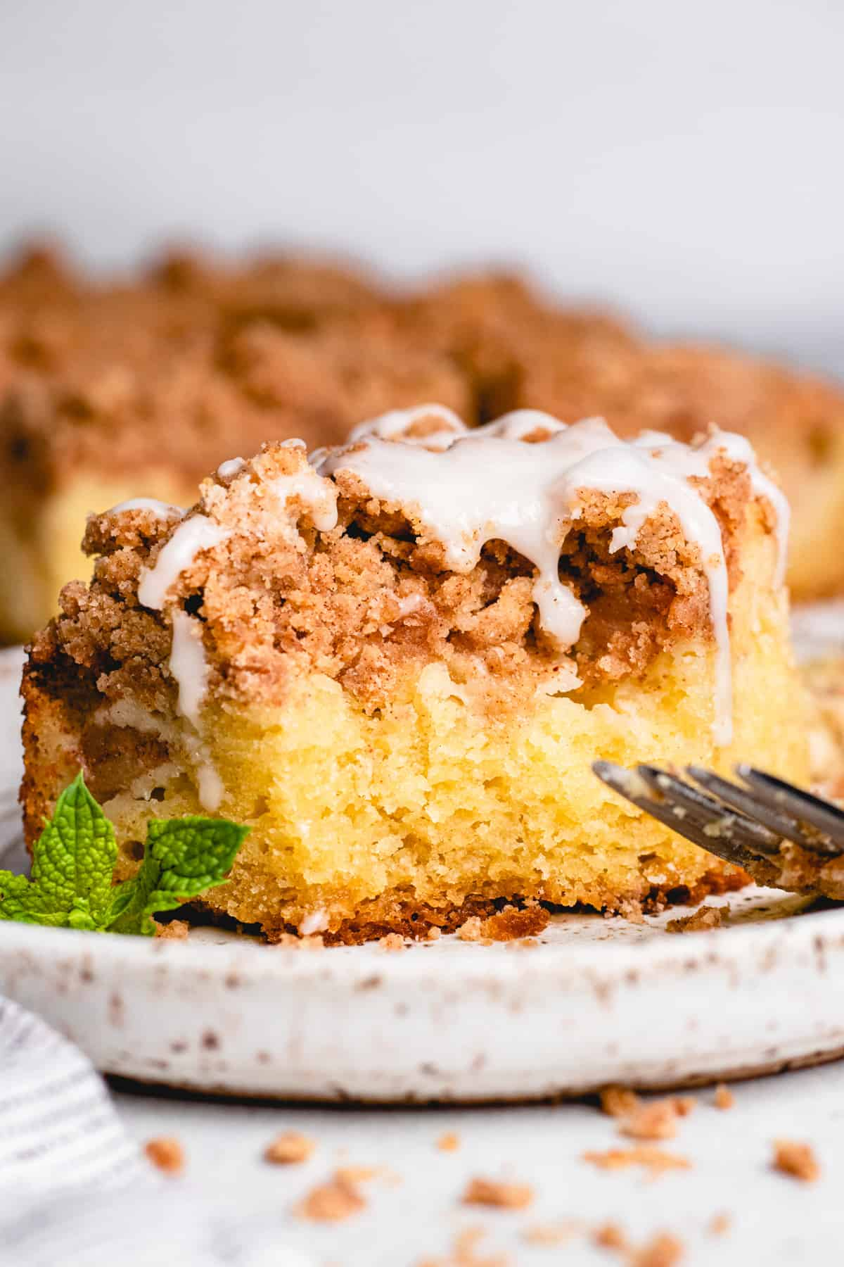 A slice of apple crumb cake on a plate with a fork and mint leaves.