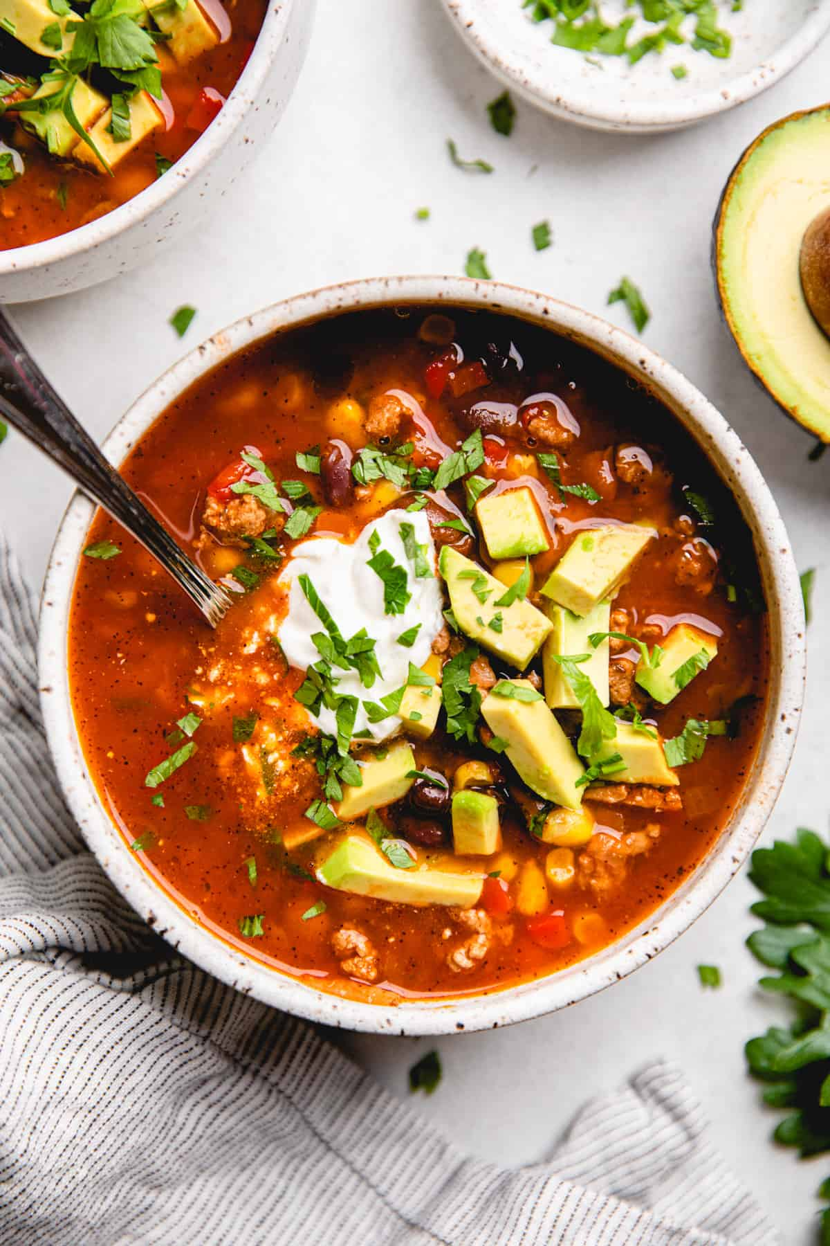 Taco Soup, topped with sour cream, avocado, and cilantro, in a white bowl.