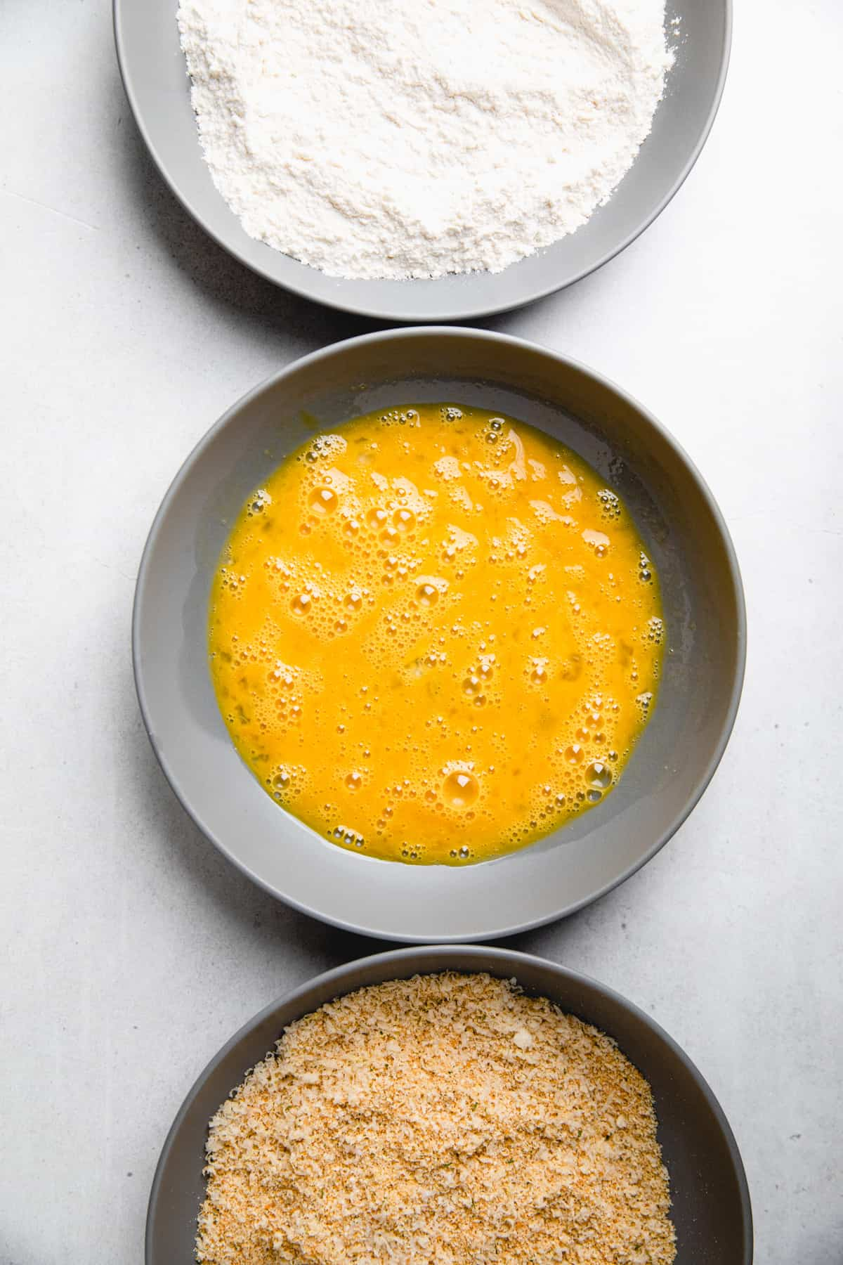 Three bowls filled with flour, eggs, and breadcrumb mixture.