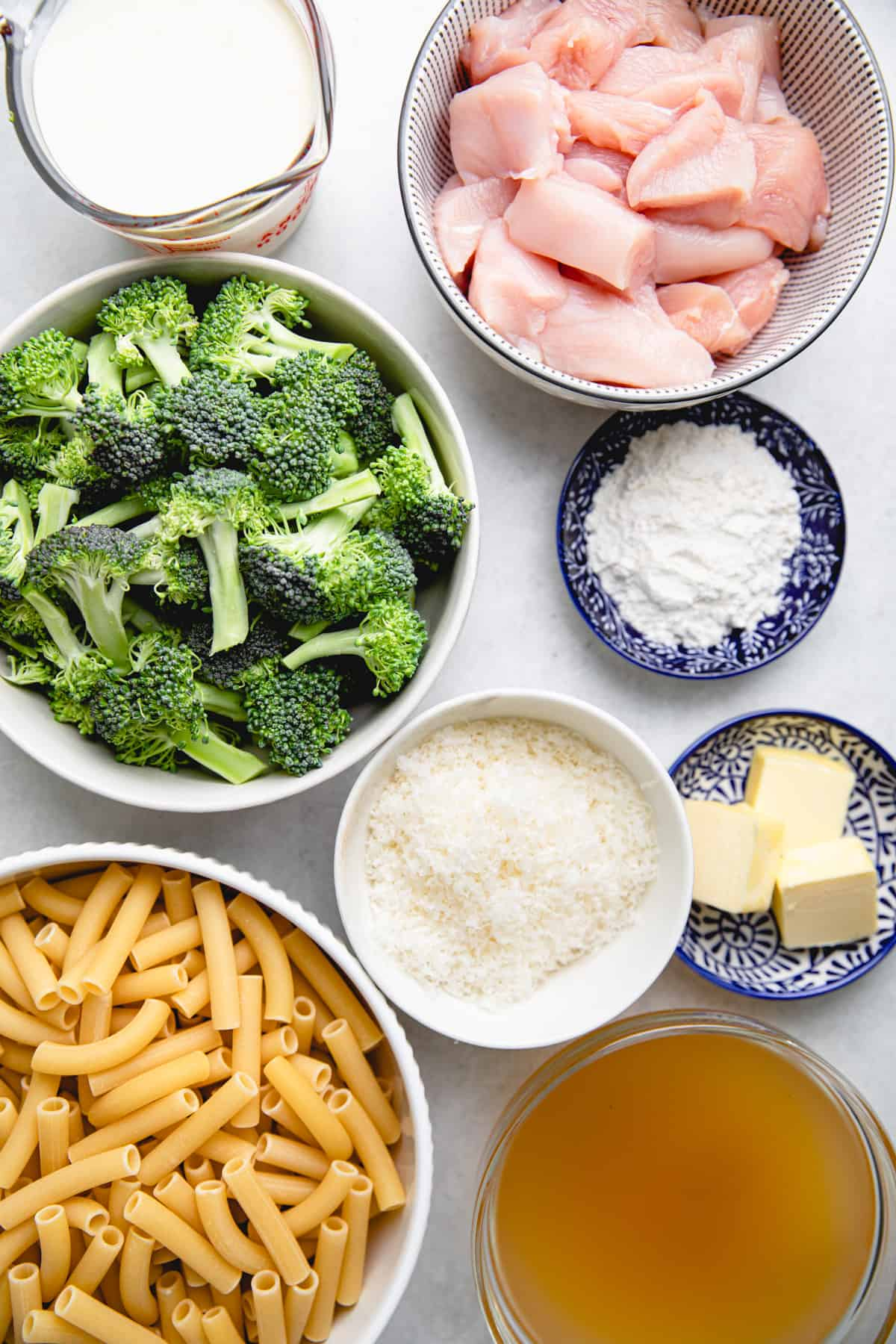 Ingredients for chicken broccoli ziti in separate bowls.