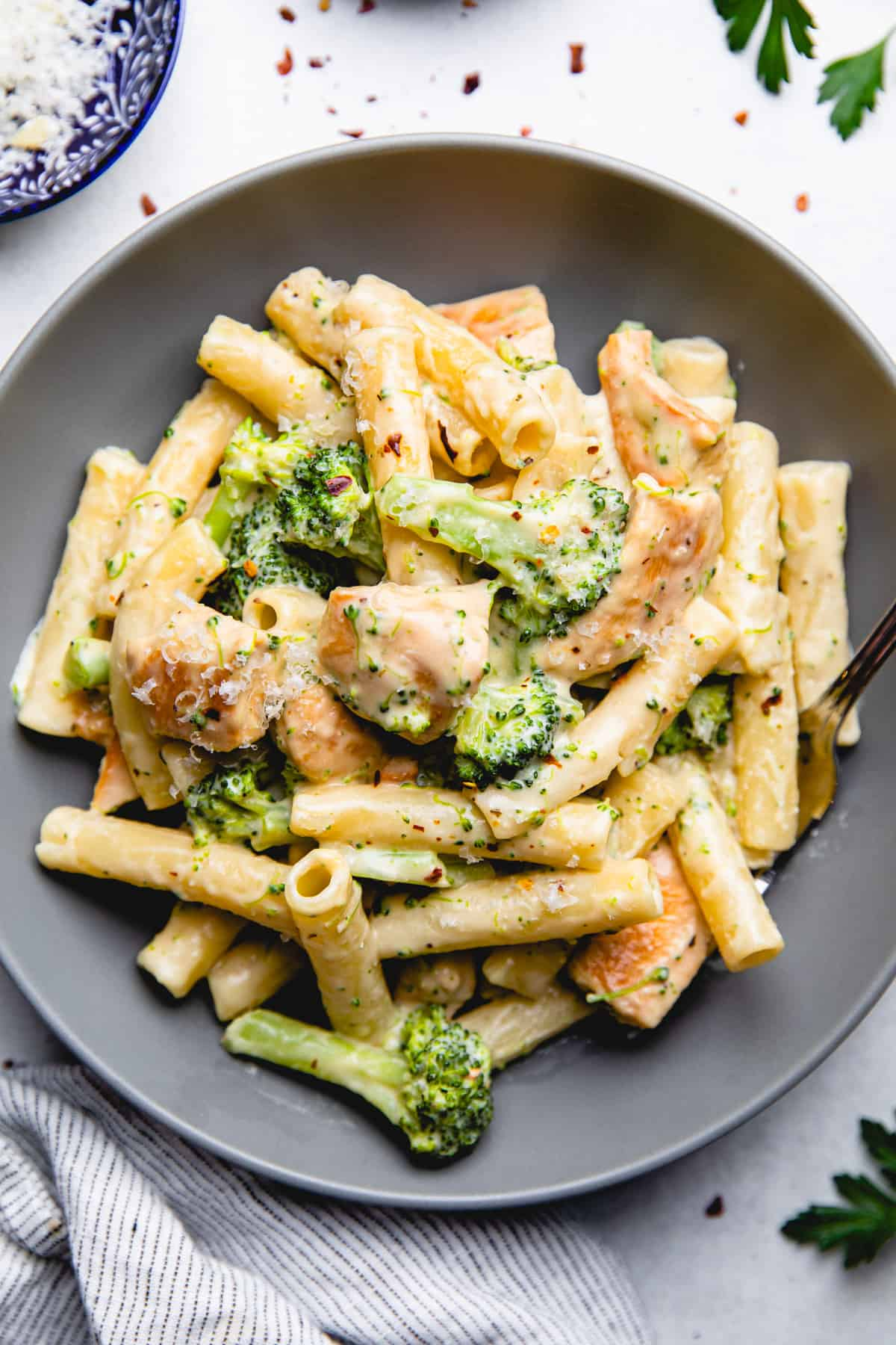 Pasta, diced chicken, and broccolli in creamy sauce in a grey plate.