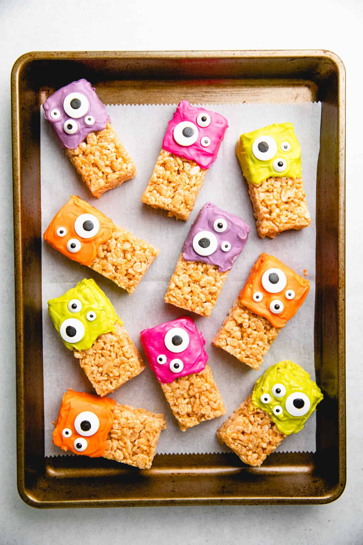 Halloween Rice Krispie Treats, topped with colored icing and candy eyes on baking sheet with parchment paper.