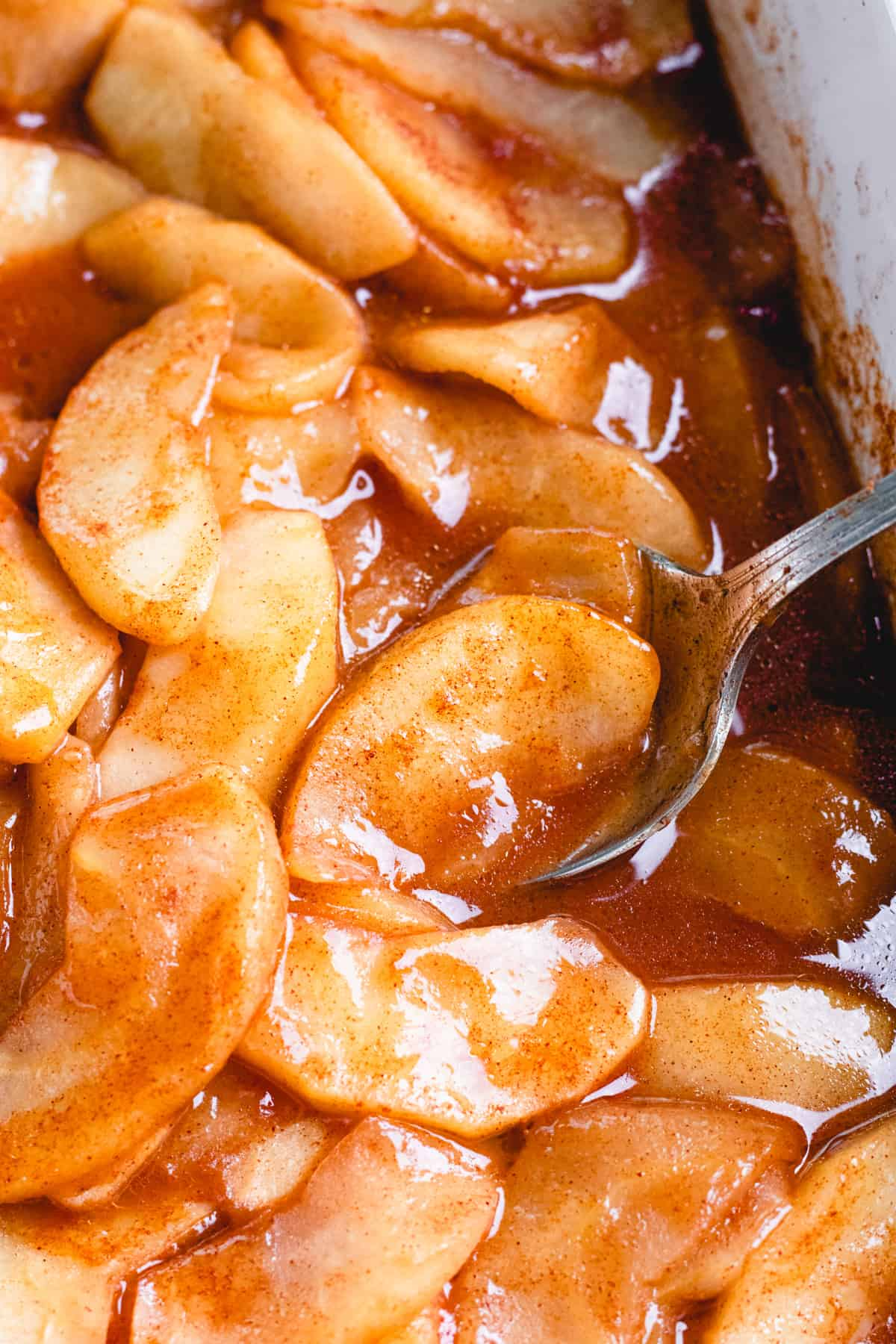 Cinnamon Baked Apples in caramelized sauce in white baking dish.