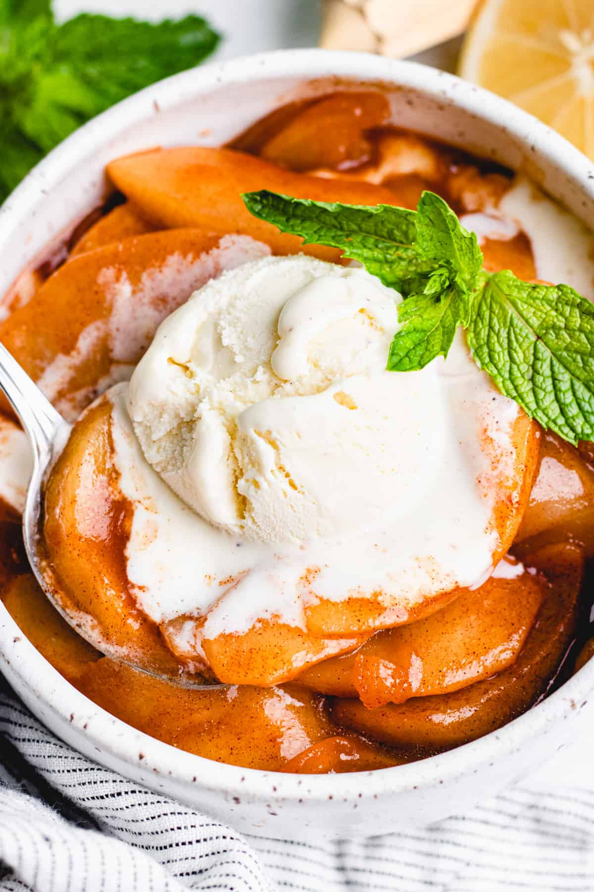 Cinnamon Baked Apple slices in a white bowl, topped with a scoop of ice cream.