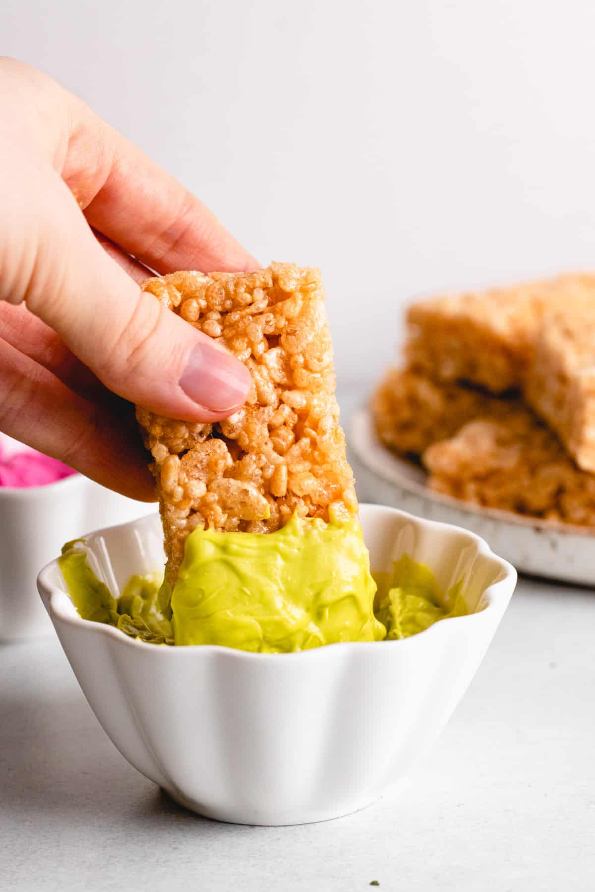Dipping a rice krispie bar into green icing.
