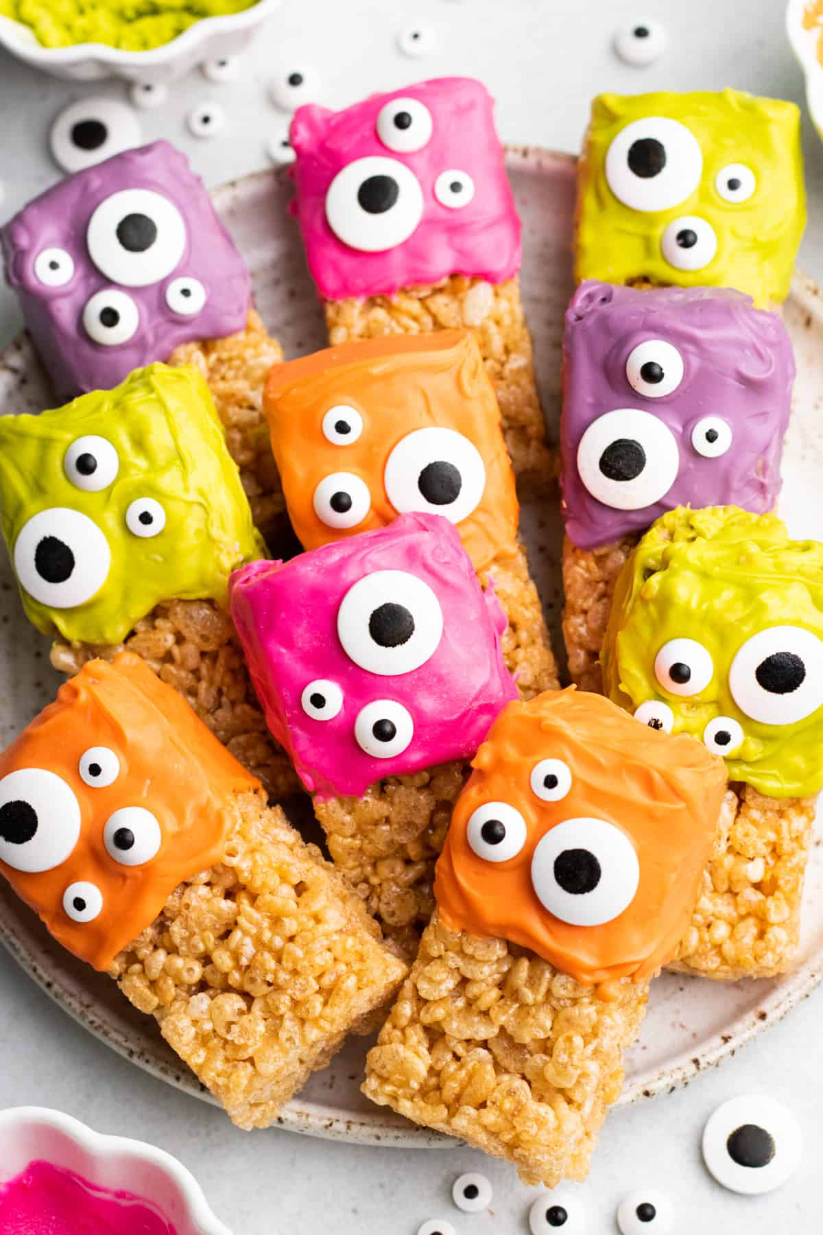 Halloween Rice Krispie Treats, topped with colored icing and candy eyes.